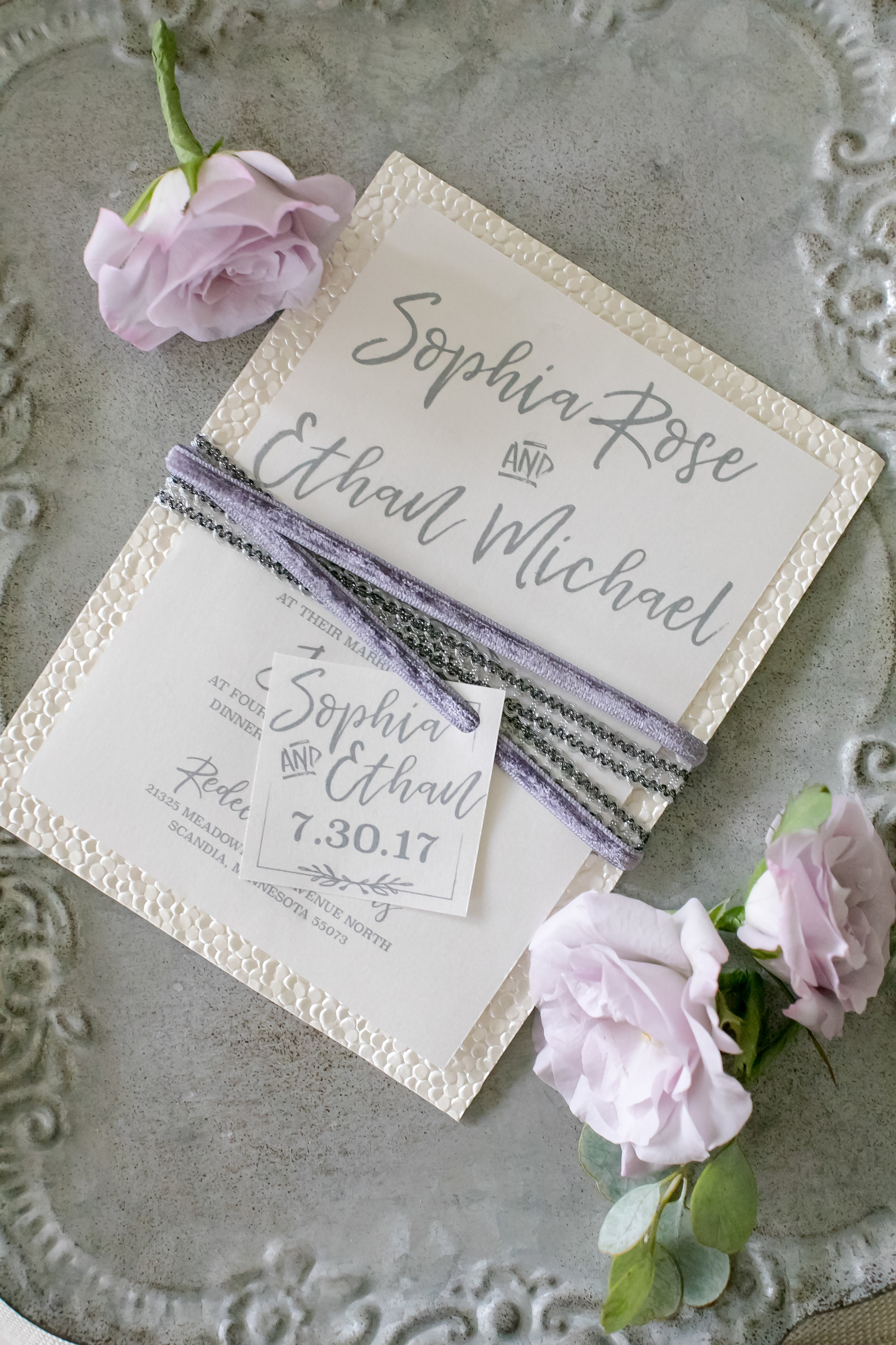 Purple and grey themed wedding invite with cursive writing