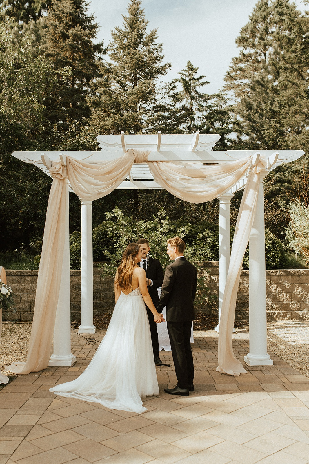 An engaged couple during the ceremony with taupe draping on their pergola