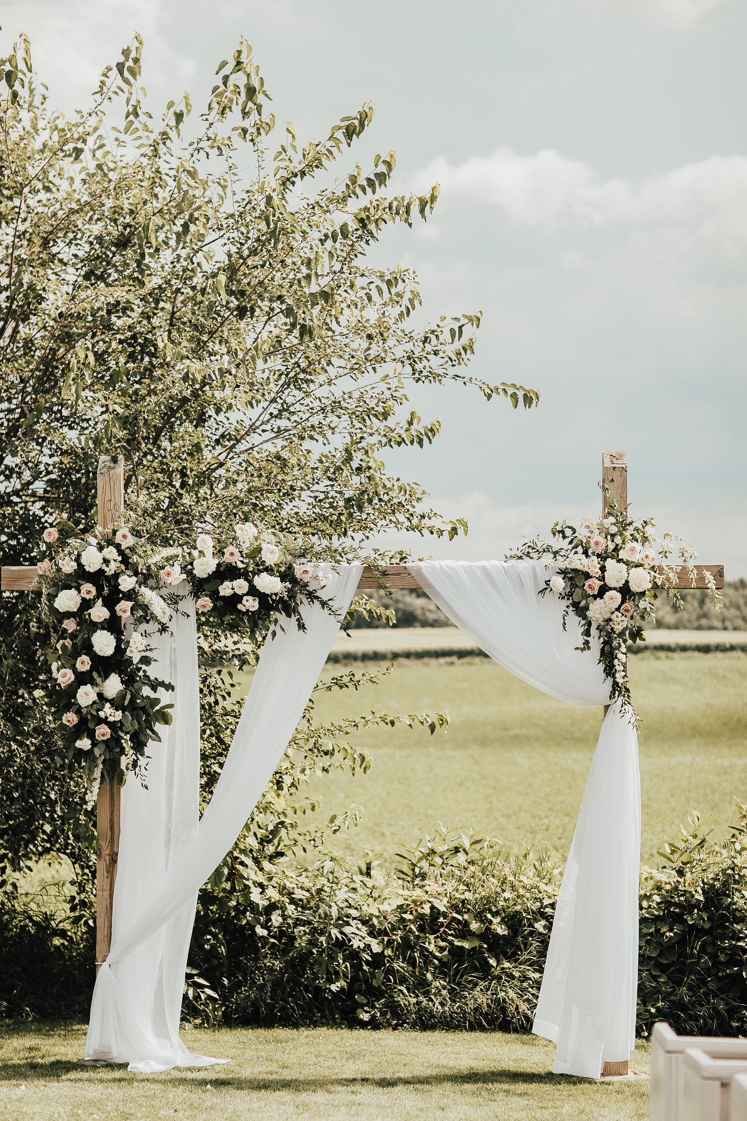 White draping on a wooden arch complimented with floral arrangements for an outdoor wedding ceremony in Minnesota.
