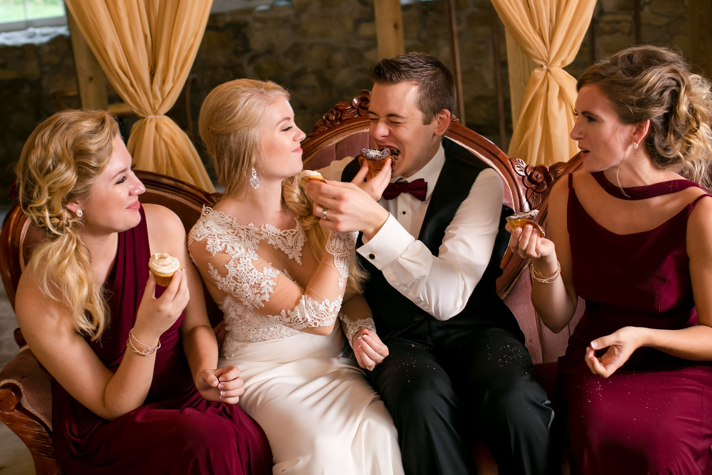 Enjoying wedding desserts with burgundy dresses and taupe draping backdrop