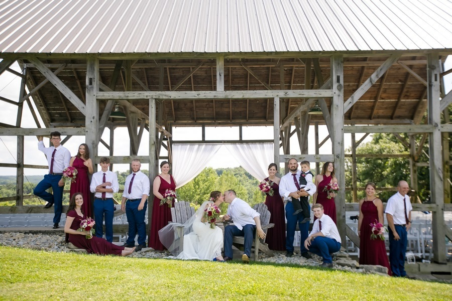 Wedding party in mismatched bridesmaid dresses taking photos in the vineyard