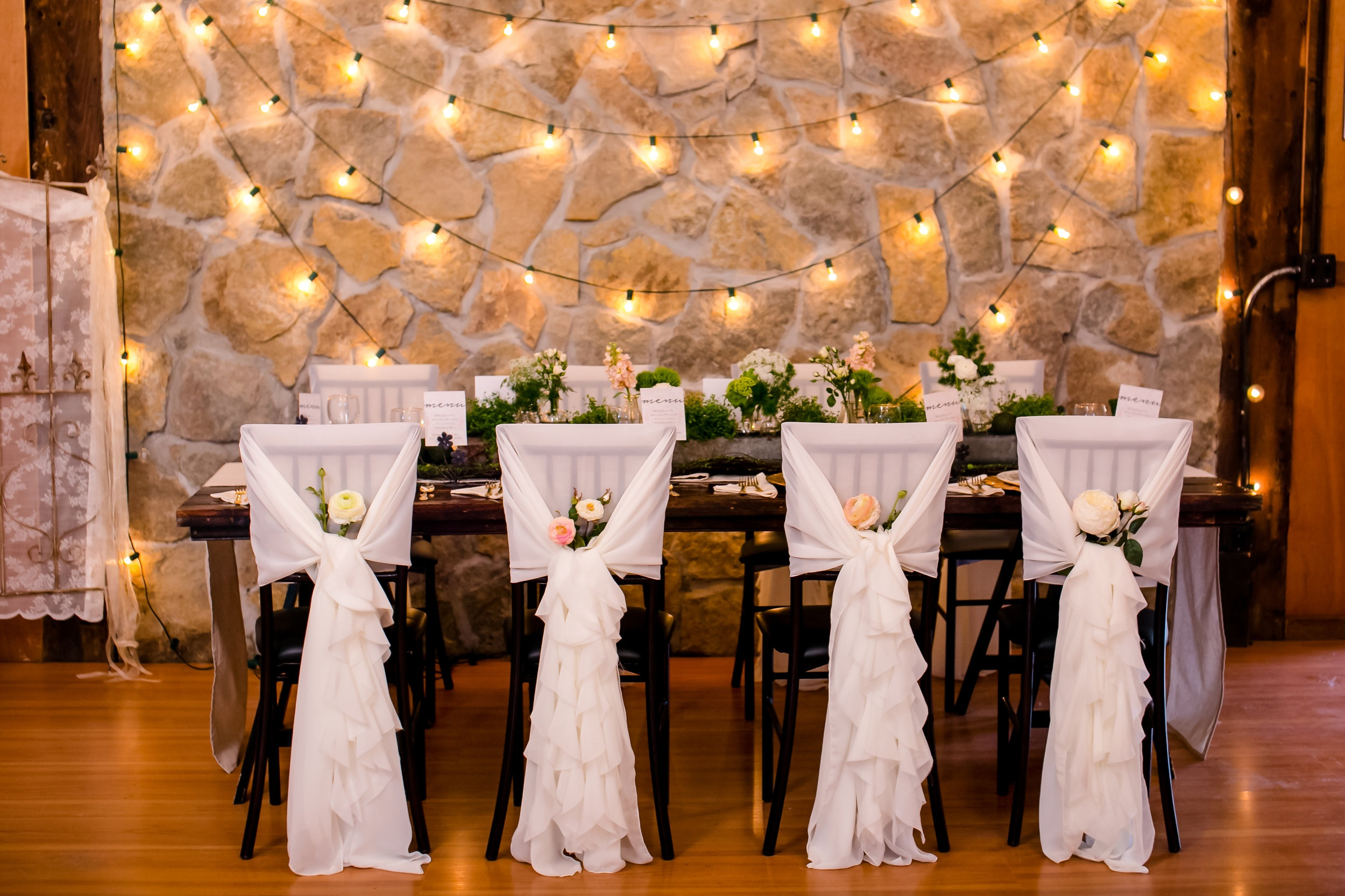 Cafe light backdrop behind the head table giving off a romantic glow