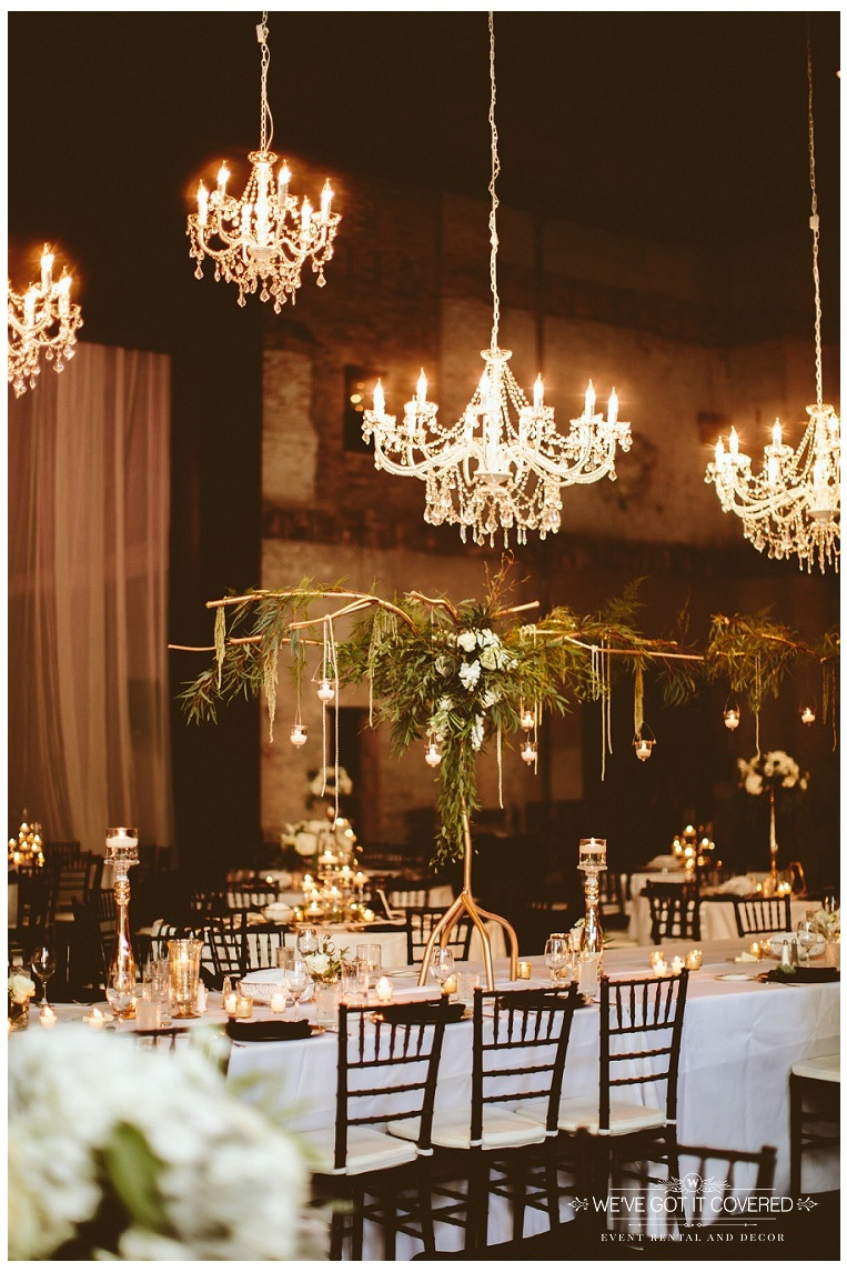 Chandelier installation over head table with a cluster of 6 different chandeliers