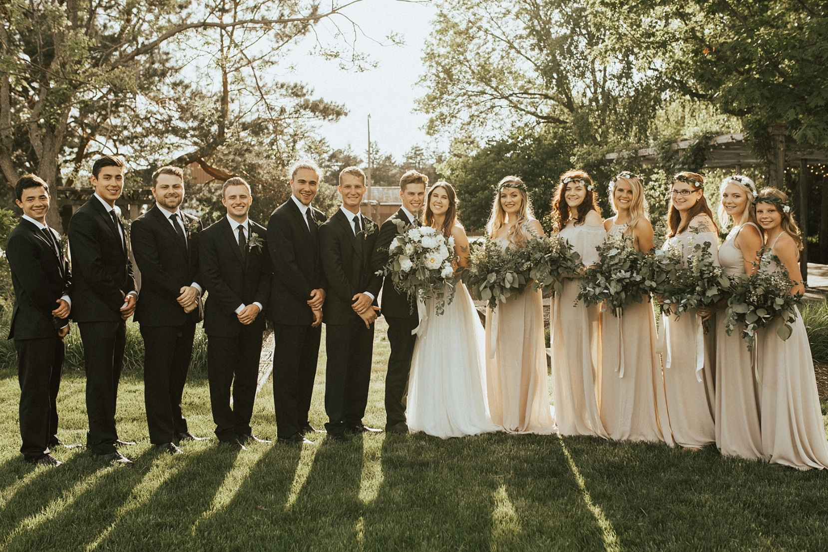 Wedding party staging photos at the Gardens of Castle Rock in Minnesota with mismatched bridesmaid dresses and taupe color palette.
