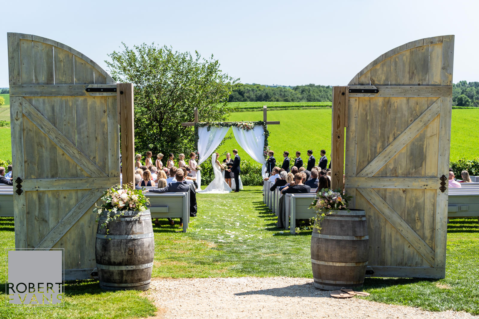 Ceremony arch decorated with white curtains pulled back and greenery to frame