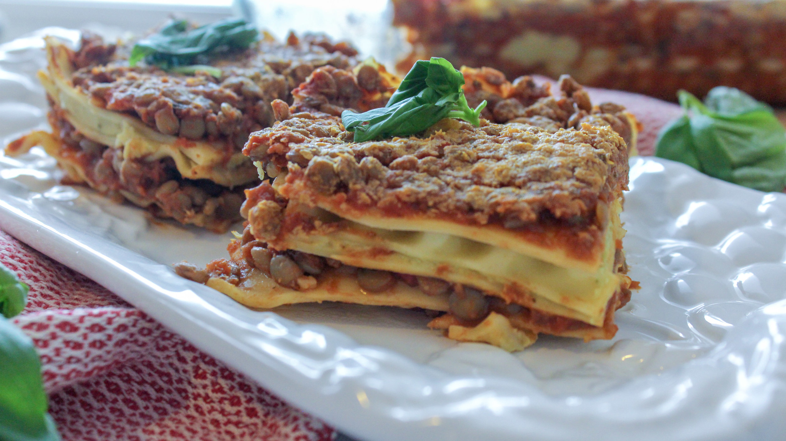 Hearty, high protein and delicious vegan lasagna. Only 10 ingredients! This will fill you up and make you feel good all at the same time. The bright flavors in the pesto ricotta add a perfect counter balance to the savory lentil pasta sauce. The flavors in this dish balance together perfectly, making a healthy, mouth watering meal. #easy #highprotein #vegan #lasagna #dairyfree