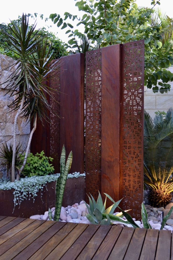 A stone feature wall, a corten steel screen and raised planter, river stones, a madagascar dragon tree, dwarf sacred bamboo, dichondra silver falls, mother-in-law's tongue, agave and sago palm.