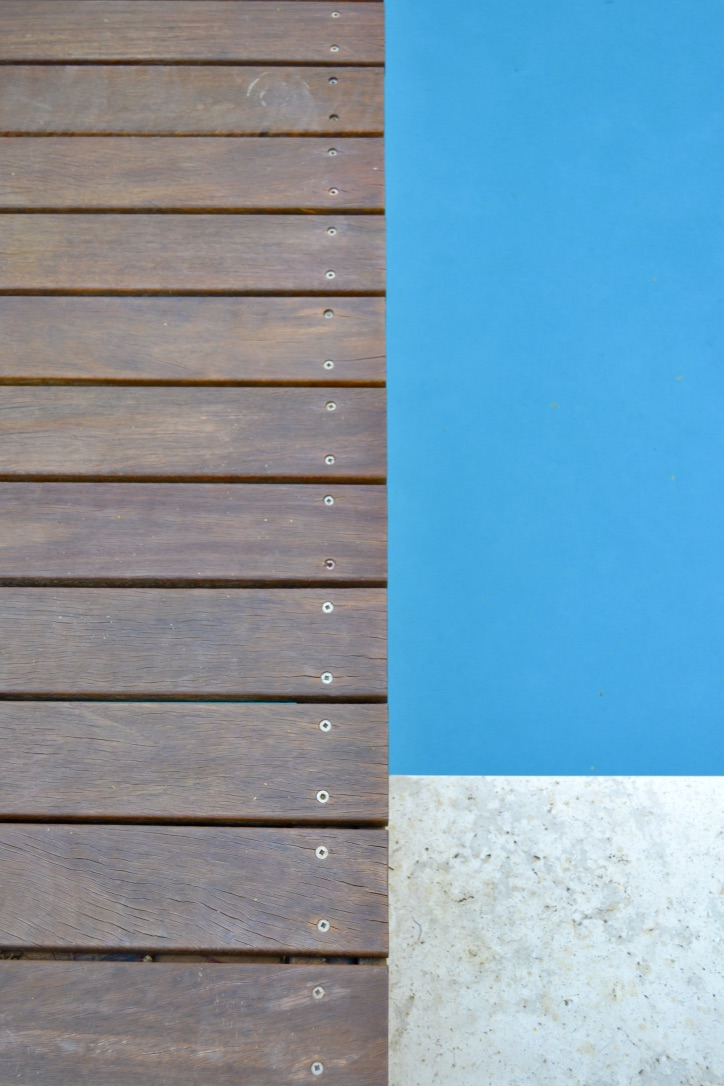 Spotted gum timber decking and travertine paving effectively frame the azure blue of the swimming pool.