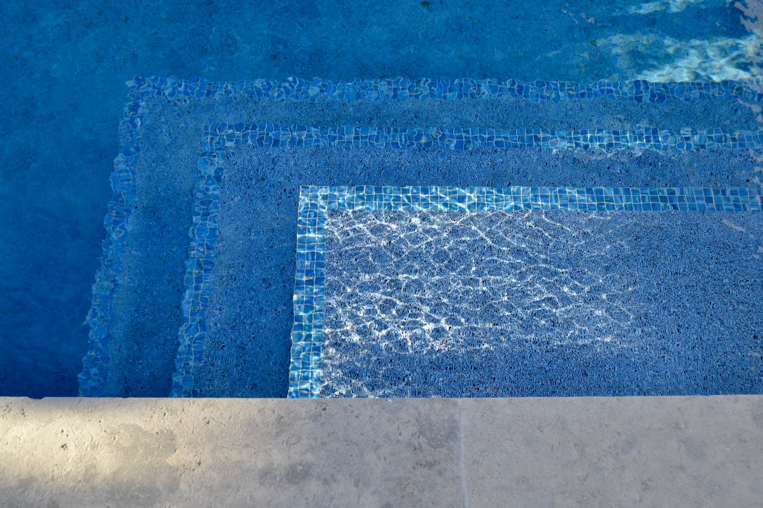 Andorra Limestone pool coping and submerged steps, lead into the sparkling blue water of this tranquil swimming pool.