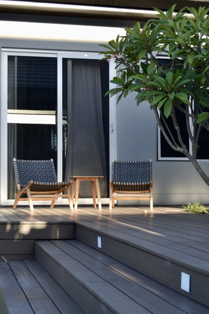 Composite timber steps lead up to this inviting seating area, where a frangipani tree provides the master suite with a green outlook and some added privacy.