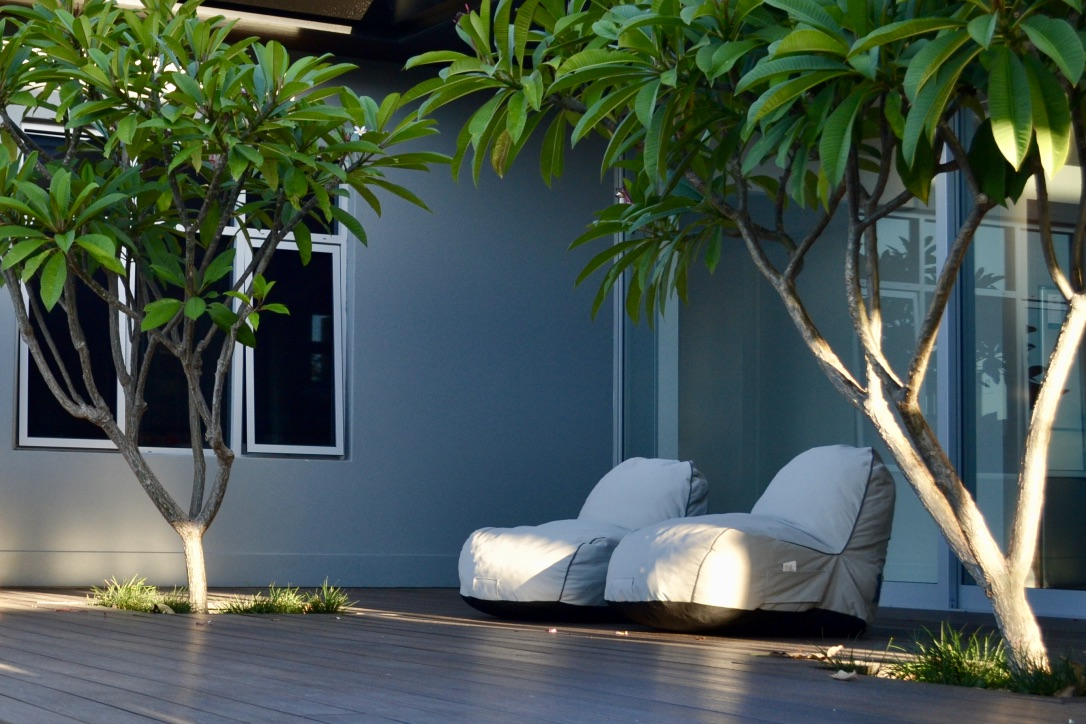 Sliding glass doors open out to this generous composite timber deck, where bean bag lounge chairs provide a comfortable place to sit under the frangipani trees.