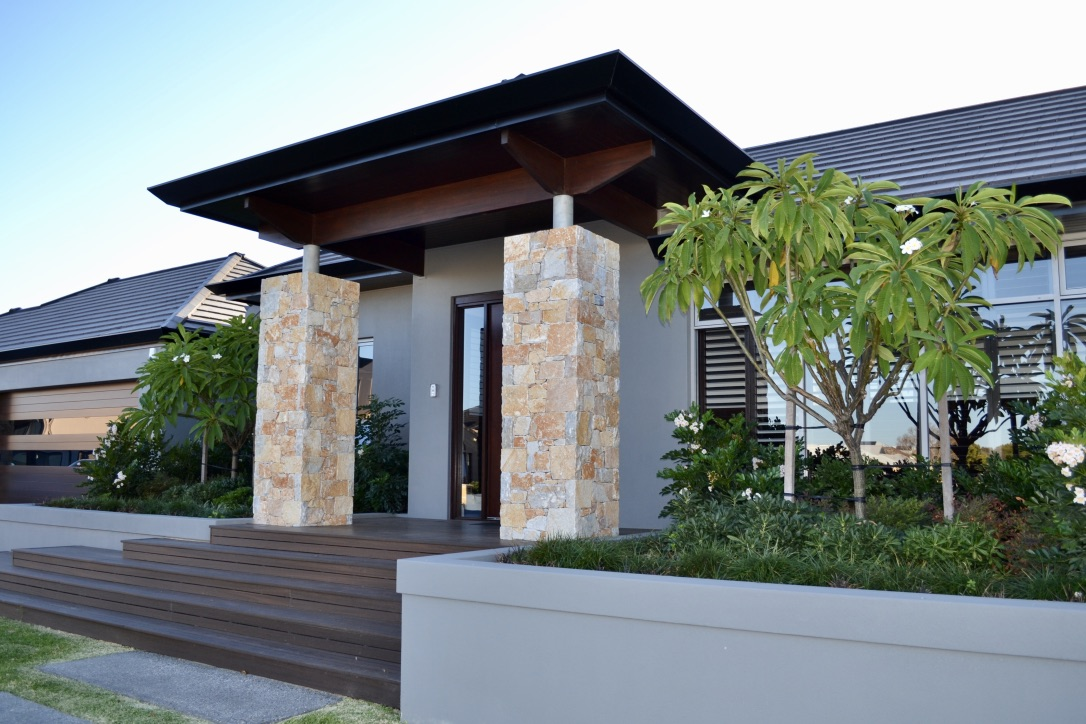 Raised rendered brick planters with central frangipani trees, mondo grass, pittosporum miss muffet, dwarf heavenly bamboo and summerscent asian bell, border the entry of this contemporary home.
