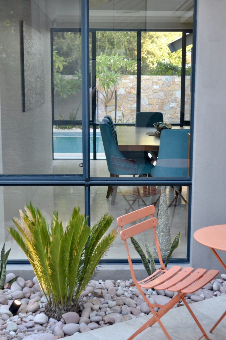 A small urban courtyard with a sago palm, mother in-law's tongue, river stones, travertine pavers, outdoor lighting and table and chairs.