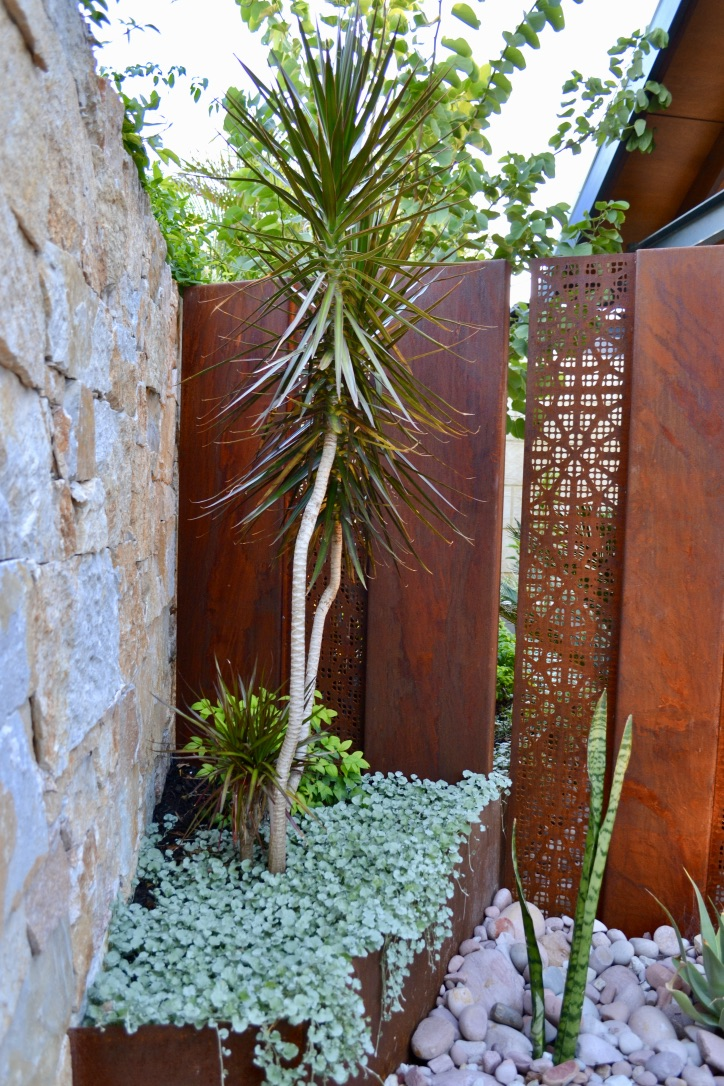 Coolum Random Ashlar stone wall cladding, corten steel and pebbles all feature in this intimate garden corner, together with mixed low maintenance plantings.