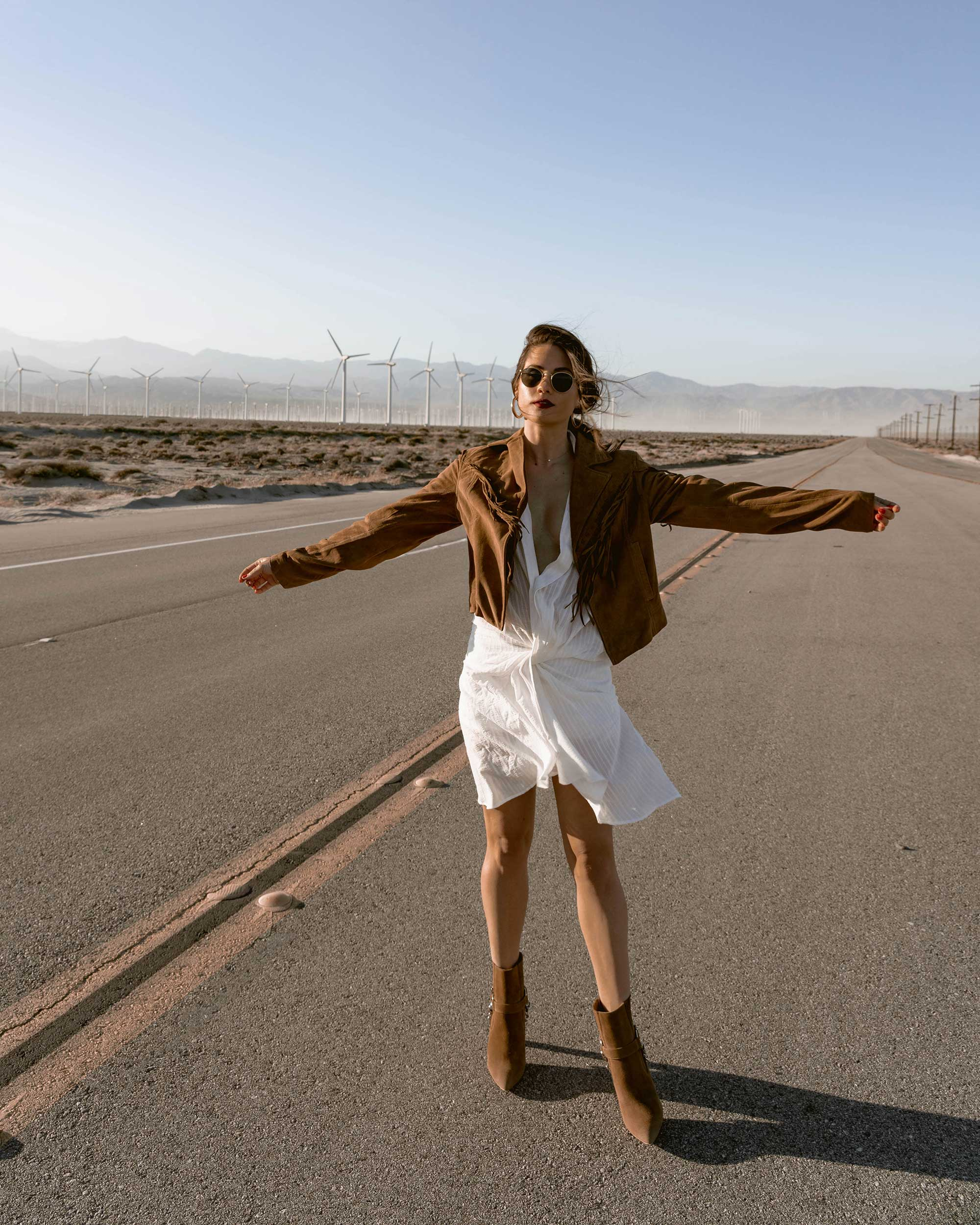 Sarah-Butler-of-Sarah-Styles-Seattle-wears-Jacquemus-Alassio-draped-white-cotton-mini-dress,-Paige-Darlene-Fringed-Suede-Jacket,-and-Paige-suede-western-boot-in-Palm-Springs-for-Coachella-Festival-Outfit-_-@sarahchristine9.jpg