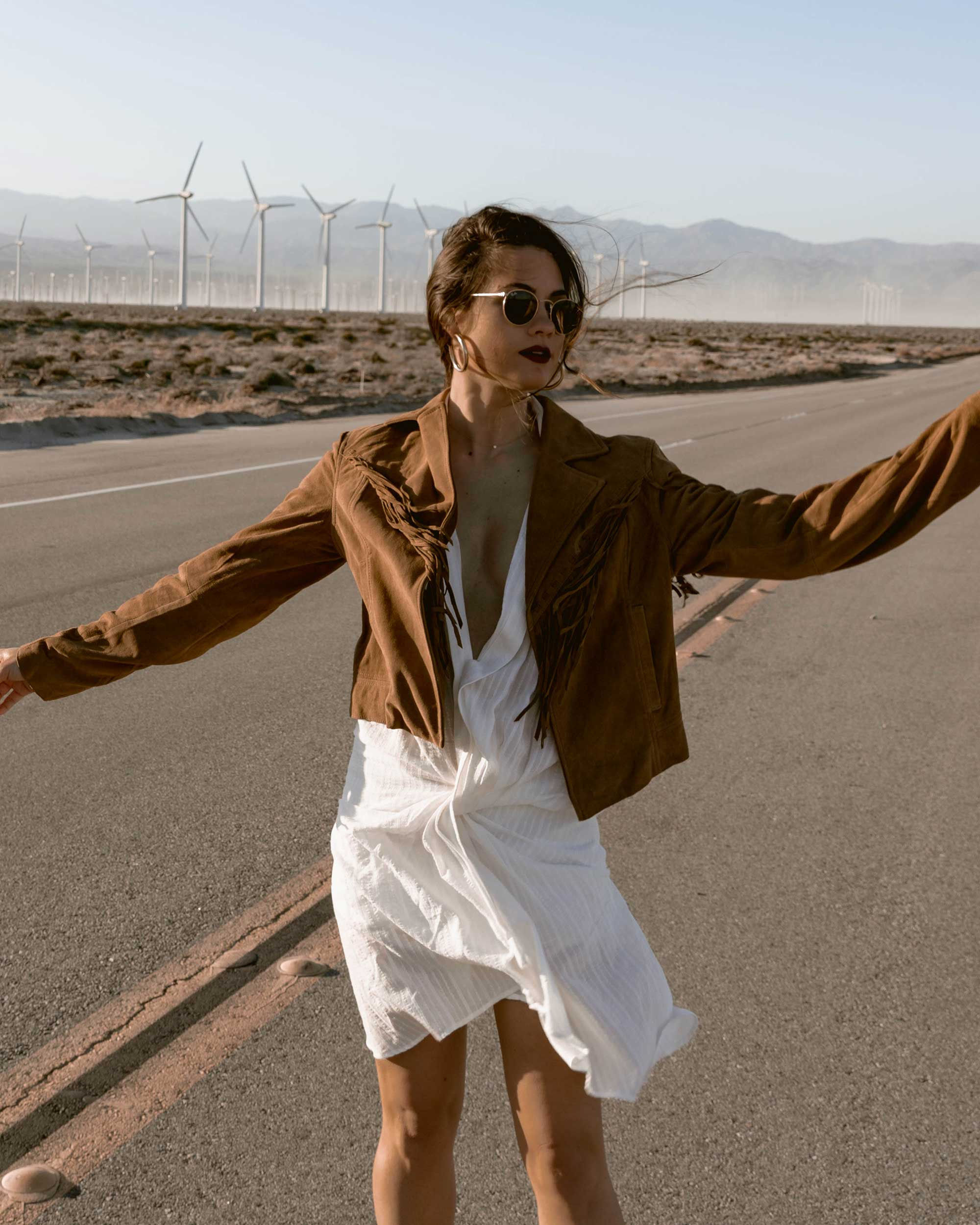 Sarah-Butler-of-Sarah-Styles-Seattle-wears-Jacquemus-Alassio-draped-white-cotton-mini-dress,-Paige-Darlene-Fringed-Suede-Jacket,-and-Paige-suede-western-boot-in-Palm-Springs-for-Coachella-Festival-Outfit-_-@sarahchristine6.jpg