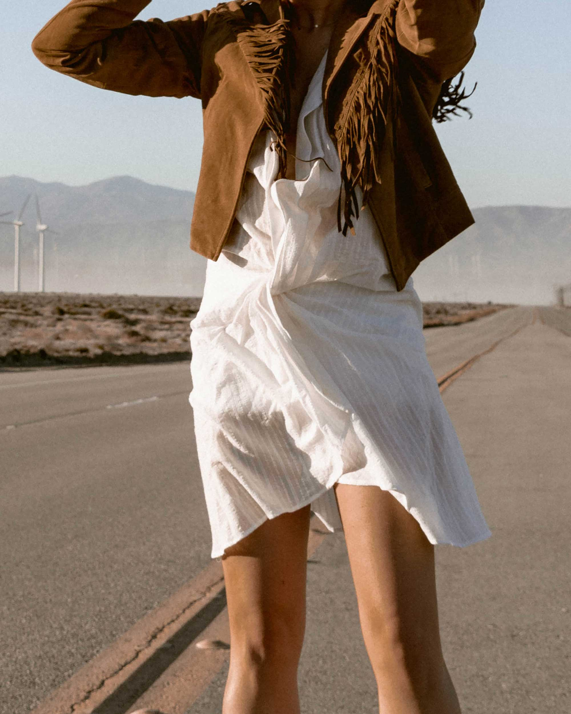 Sarah-Butler-of-Sarah-Styles-Seattle-wears-Jacquemus-Alassio-draped-white-cotton-mini-dress,-Paige-Darlene-Fringed-Suede-Jacket,-and-Paige-suede-western-boot-in-Palm-Springs-for-Coachella-Festival-Outfit-_-@sarahchristine2.jpg