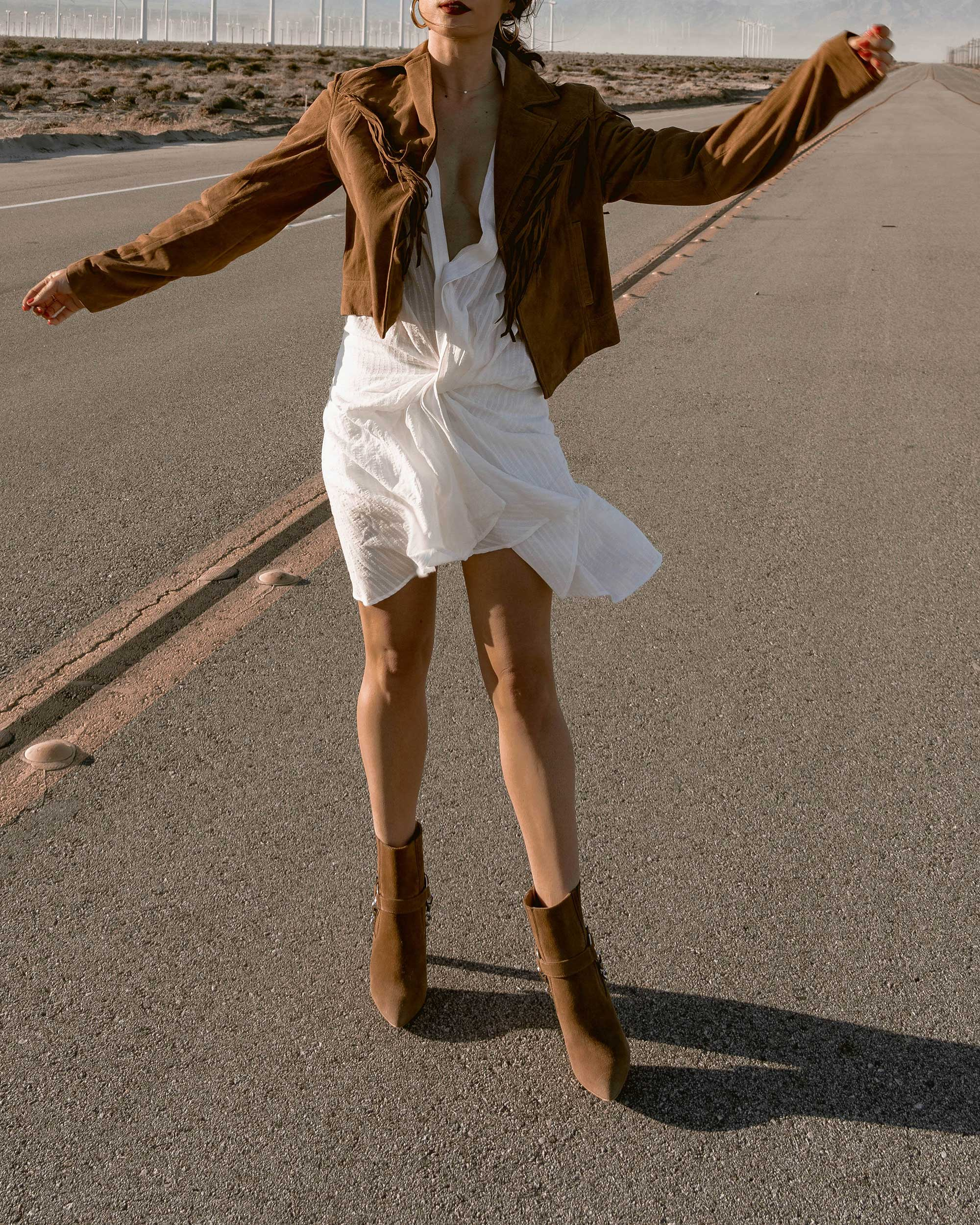 Sarah-Butler-of-Sarah-Styles-Seattle-wears-Jacquemus-Alassio-draped-white-cotton-mini-dress,-Paige-Darlene-Fringed-Suede-Jacket,-and-Paige-suede-western-boot-in-Palm-Springs-for-Coachella-Festival-Outfit-_-@sarahchristine8.jpg