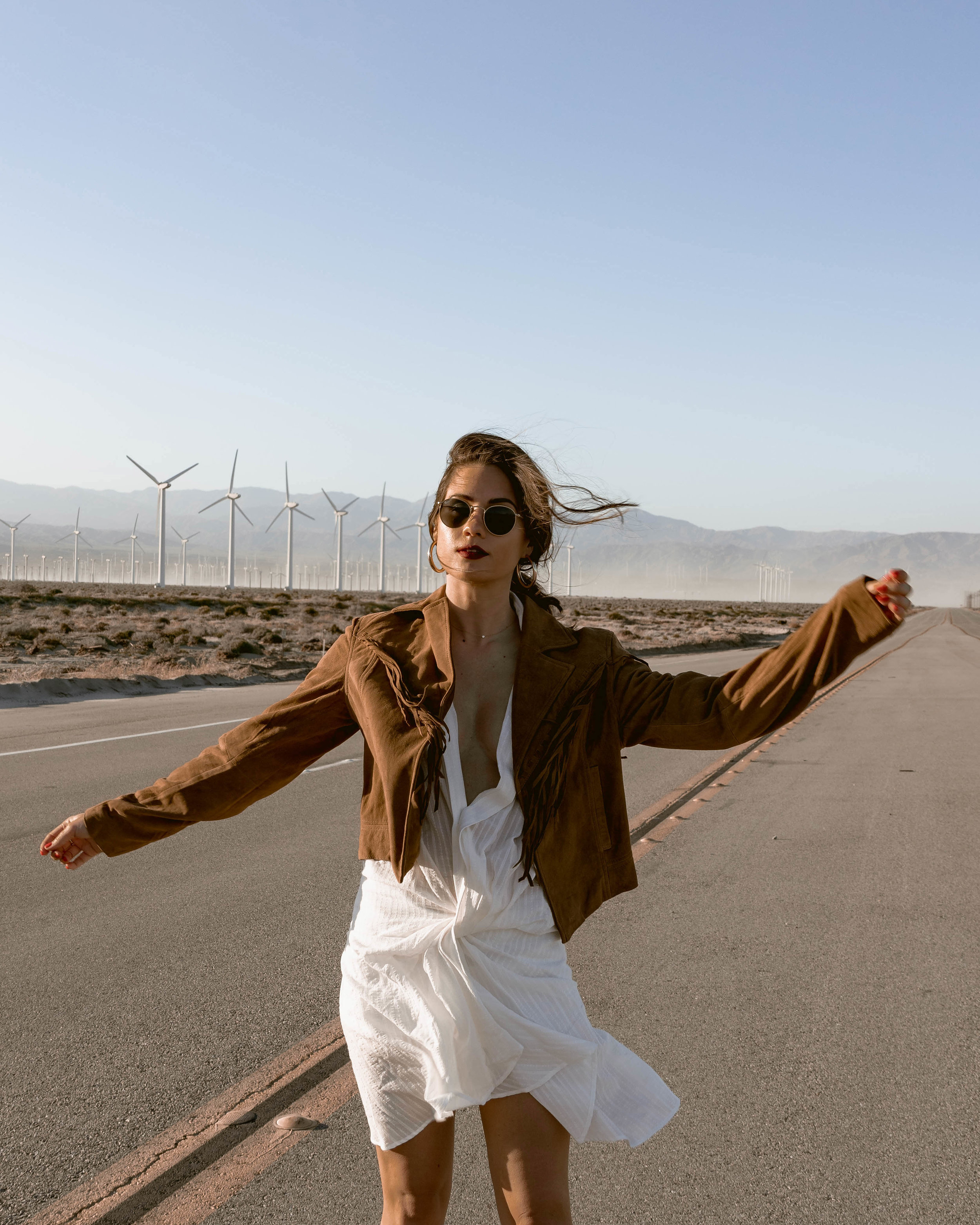 Festival Fringe - Jacquemus Alassio draped white cotton mini dress, Paige Darlene fringed suede jacket and Paige suede western boot in Palm Springs for Coachella festival outfit