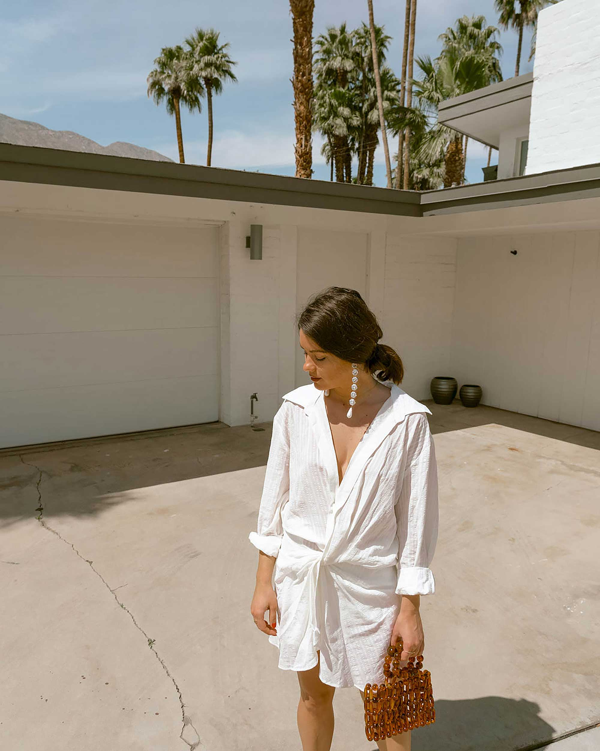 Sarah Butler of Sarah Styles Seattle wears Jacquemus Alassio draped white cotton mini dress and Cult Gaia Acrylic Cora Clutch in tortoise shell brown Palm Springs Outfit | @sarahchristine 6.jpg