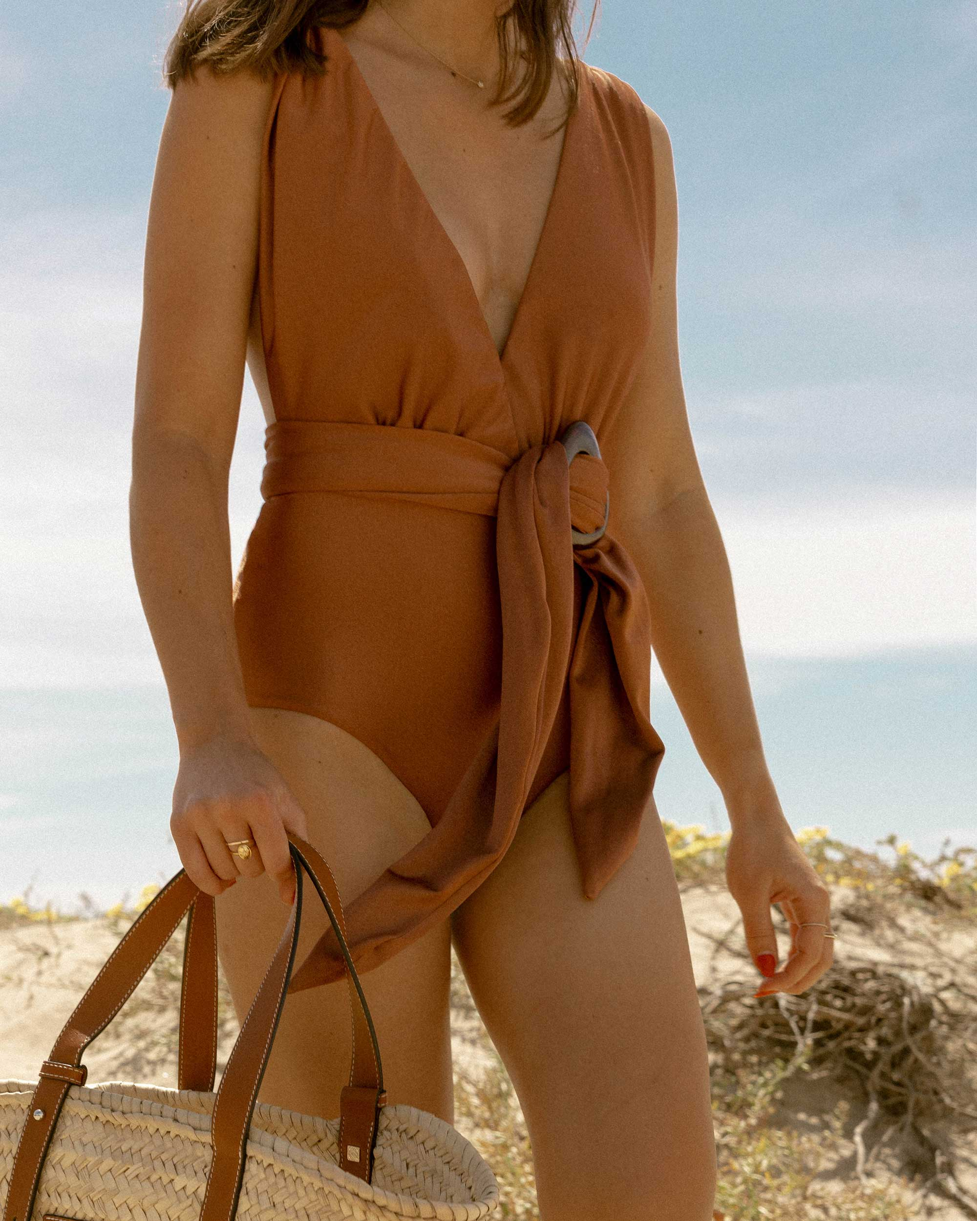 Oceanside in Newport Beach - Patbo solid brown belted swimsuit and Loewe small raffia basket tote bag for the perfect summer beach look