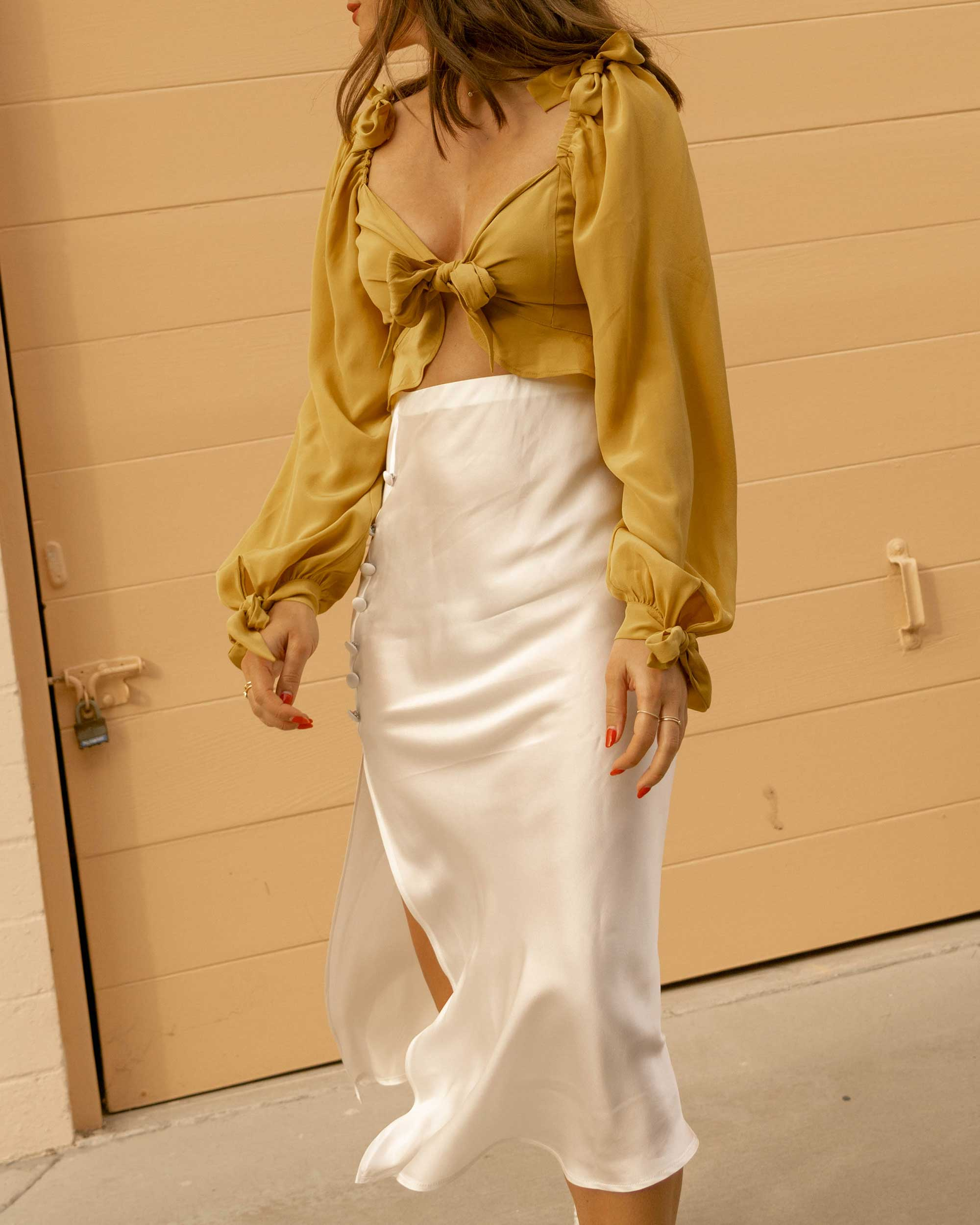 Click to shop outfit + more photos! Sarah Butler of Sarah Styles Seattle wears Yellow bell sleeve crop top and side slit silk midi skirt in Newport Beach, California for the perfect summer outfit | @sarahchristine - 1.jpg