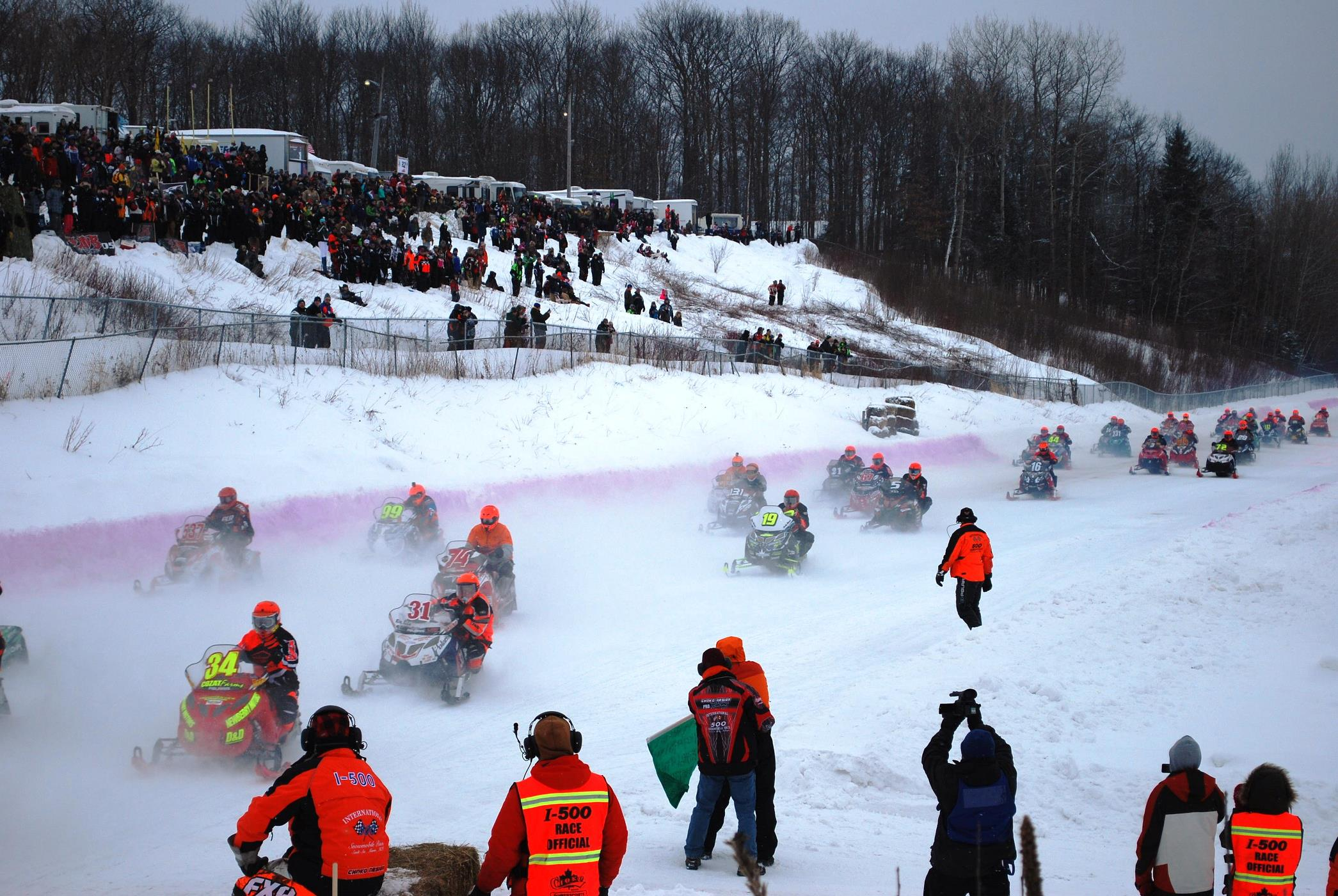 Photo credit: Fans and race officials look on as participants in the annual I-500 snowmobile competition vie for the finish line. [Image courtesy of Great Getaways]