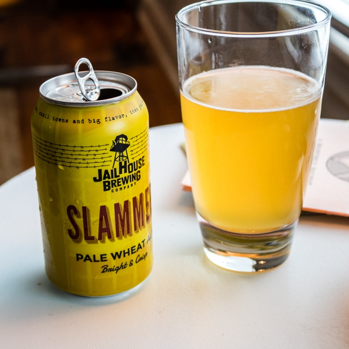 "Bright, crisp and citrusy, with just a touch of tartness, Slammer is brewed from a pilsner malt foundation with just the right amount of wheat to provide body and depth. Lightly hopped to balance the delicate malt character, Slammer Wheat is the perfect craft beer for the ""general population."""