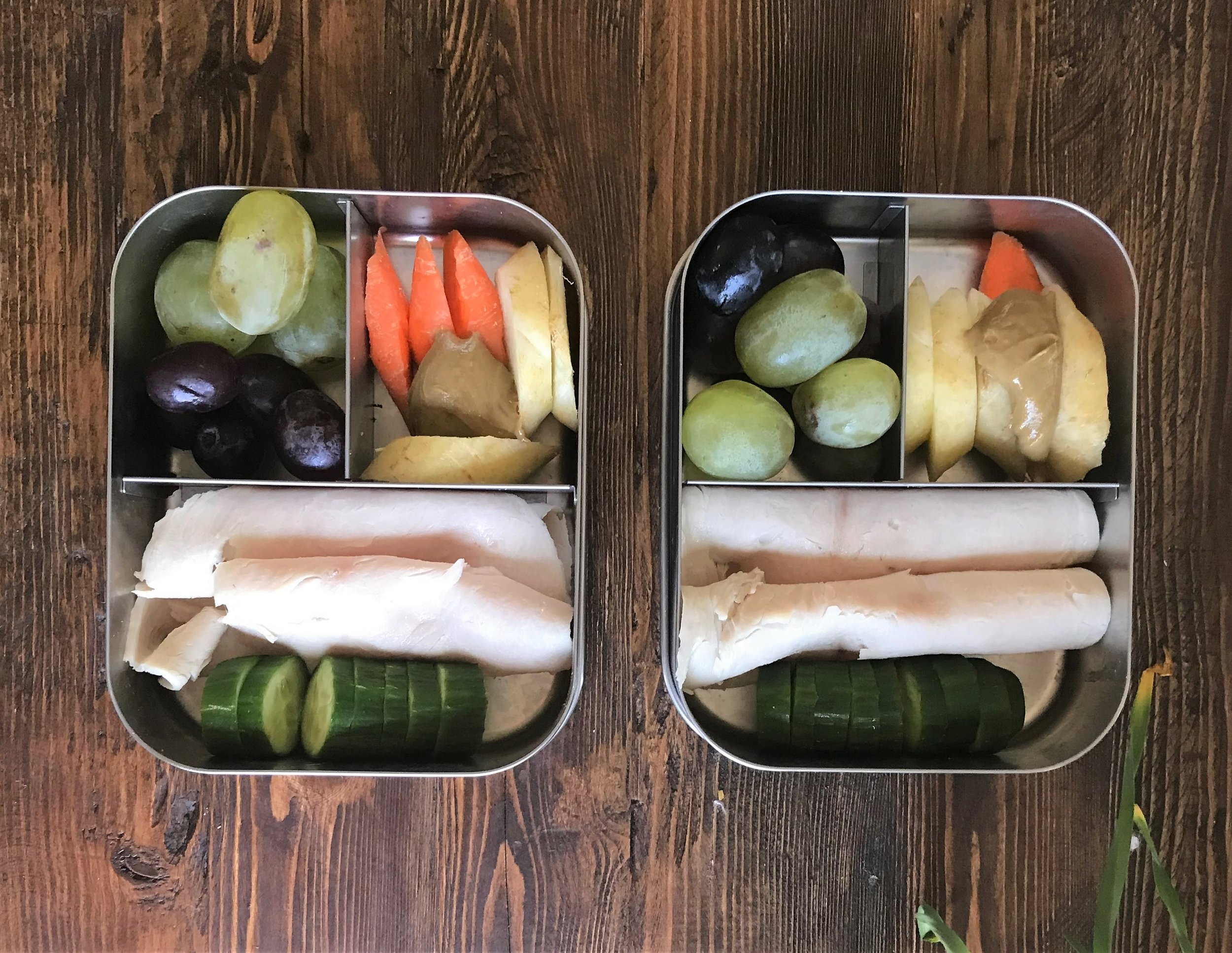 Bottom: Turkey, cucumbers  Left corner: green and purple grapes  Right corner: carrots and sunflower butter