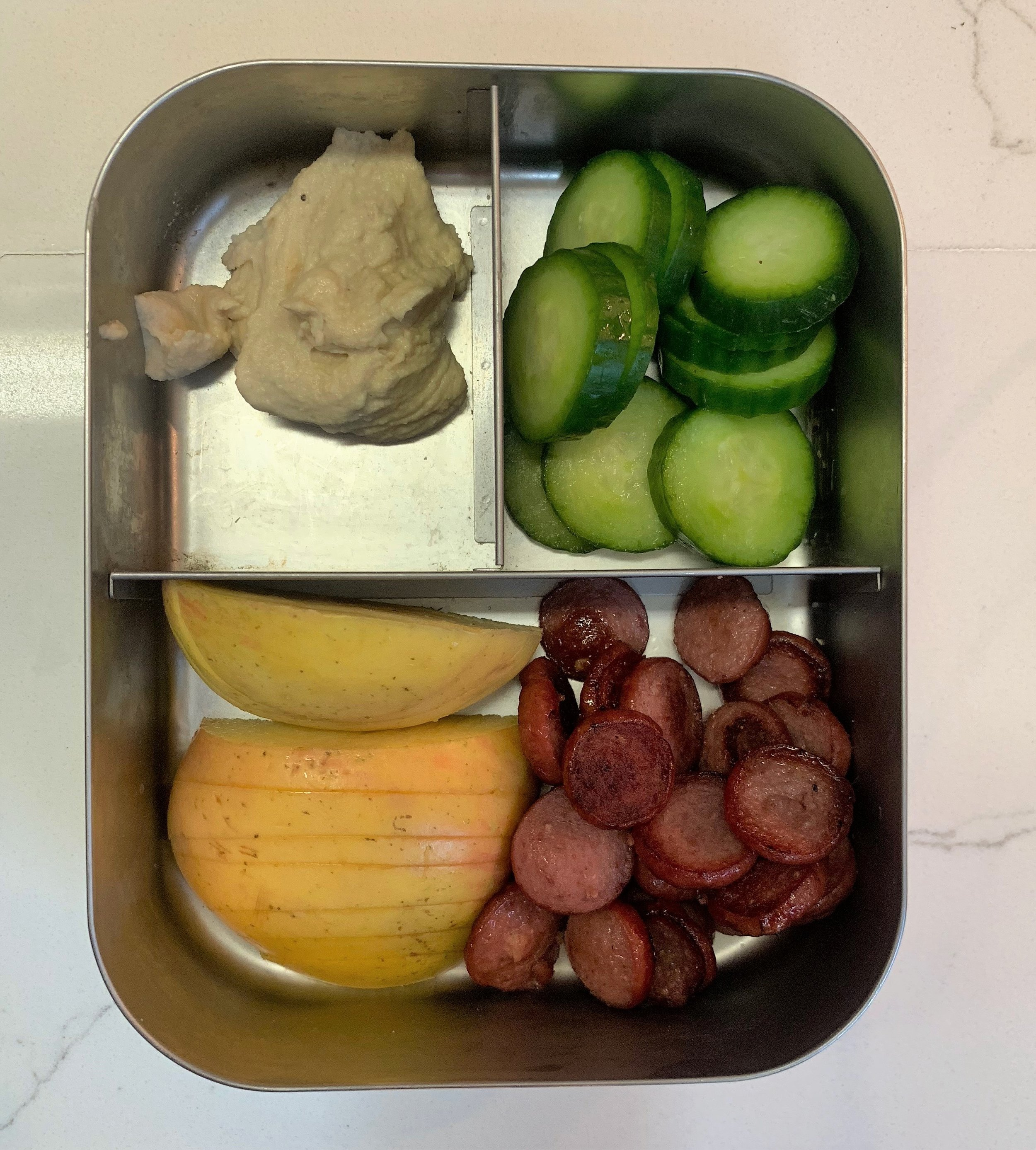 Main section: half and apple and some organic turkey hot dog slices  Top left: hummus  Top right: cucumbers