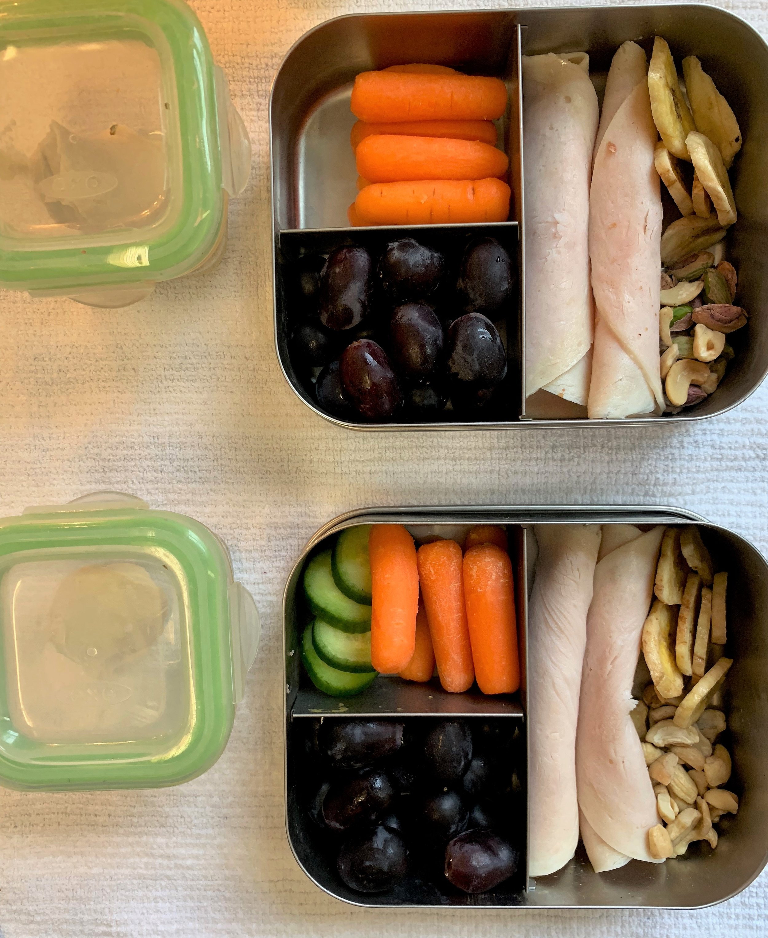 Main: Turkey, banana chips, cashews  Bottom left: grapes  Top left: cucumbers and carrots  Extra container: hummus