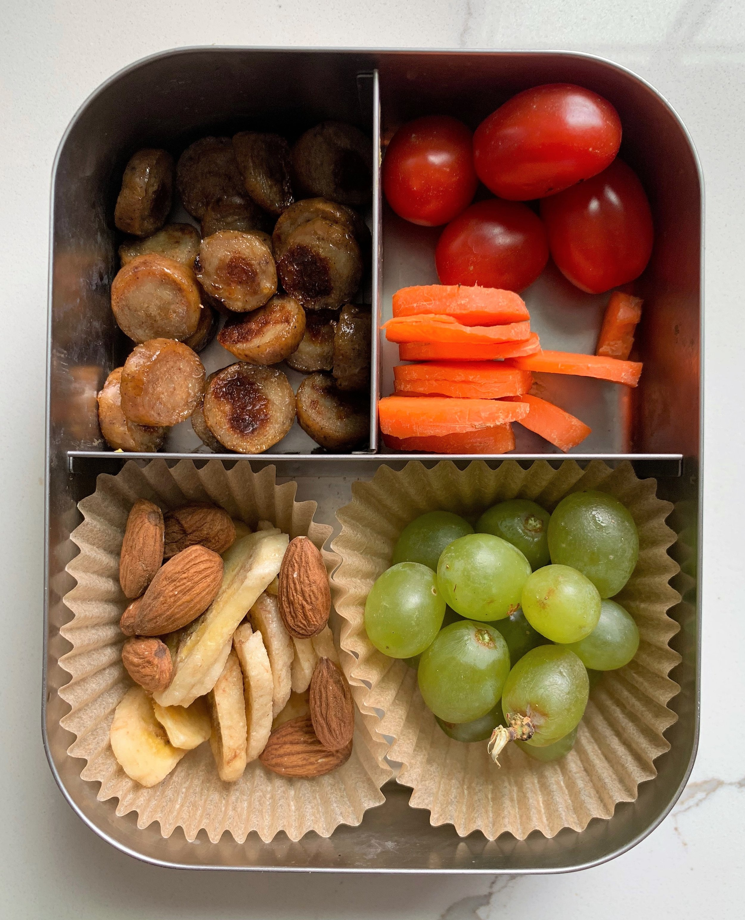 Top left: organic turkey hot dog  Top right: Carrots and tomatoes  Bottom left: banana chips and almonds  Bottom right: grapes