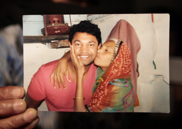 A photograph of Saroo Brierley, reunited with his family. His mother is hugging and kissing him.