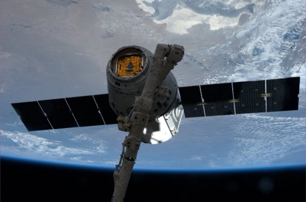 The robotic arm grapples the Dragon. Photo courtesy of NASA.