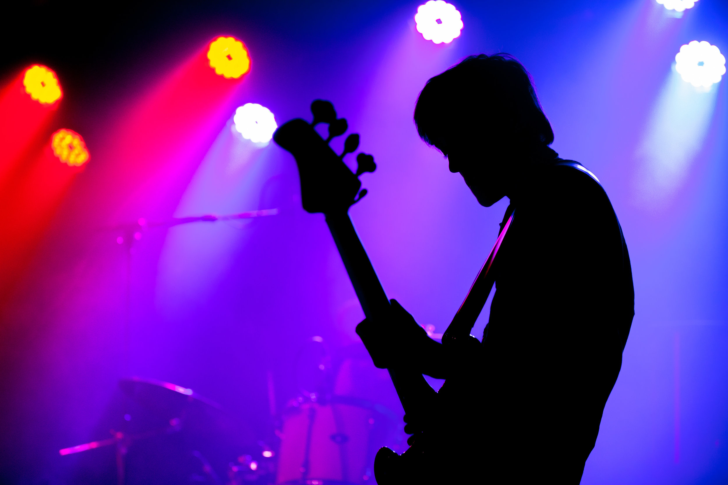 Shane Findlay silhouetted with his bass guitar.   Photo by Donal Lakatua
