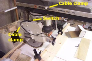 3. Attach the switch to the top of the guard.  4. Attach one cable clamp to the blade guard as shown  5. With the saw in the back position find a point about 1/3 the way down the slide to mount the second cable clamp. Hold the wire by hand and move the saw from front to back to make sure the the cable is not stretched tight. Attach the cable clamp to this position.  6. Use the cable ties to attach the Laserkerf power cable to the saw power cable.