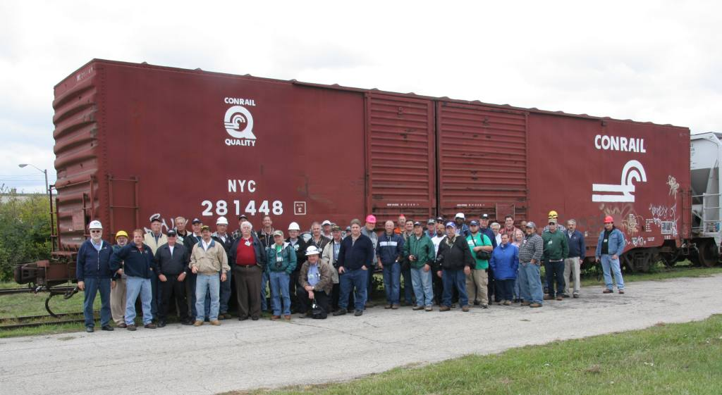 Group photo of attendees in front of an ex-PC X82 boxcar