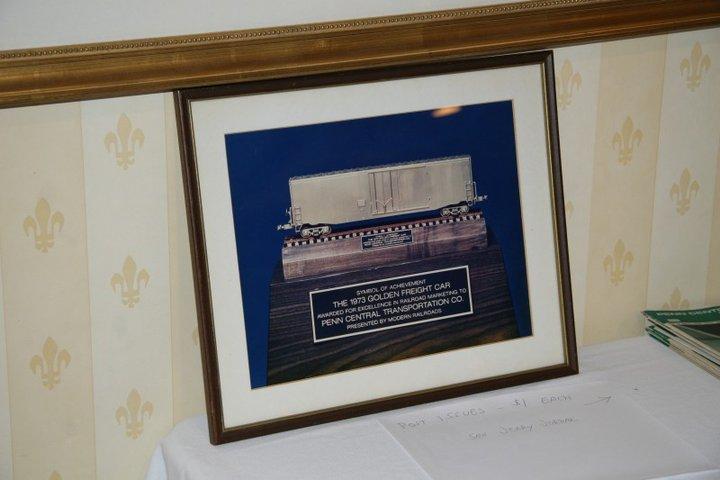 "A framed photo of the Penn Central's ""Golden Freight Car"" award"