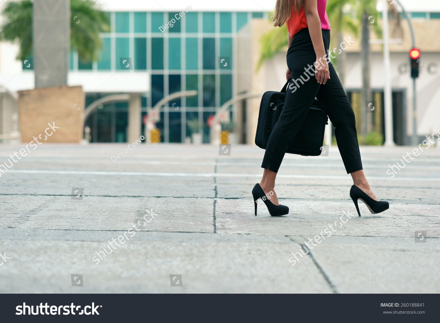 stock-photo-cropped-view-of-business-woman-walking-in-city-street-with-laptop-bag-commuting-and-going-to-work-260188841.jpg