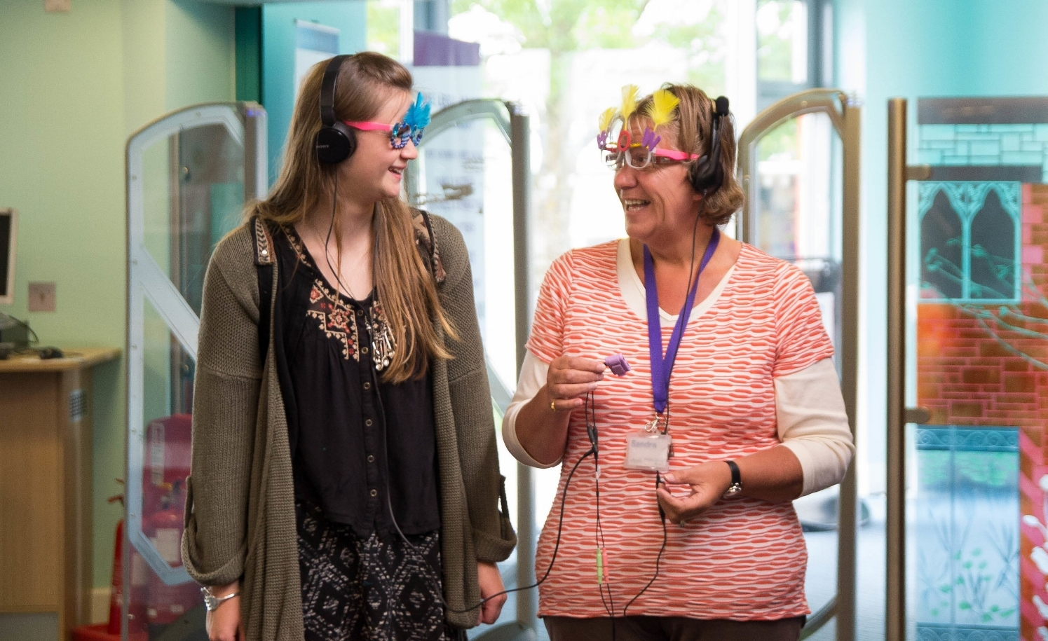 Two audience members take an audio tour of the library