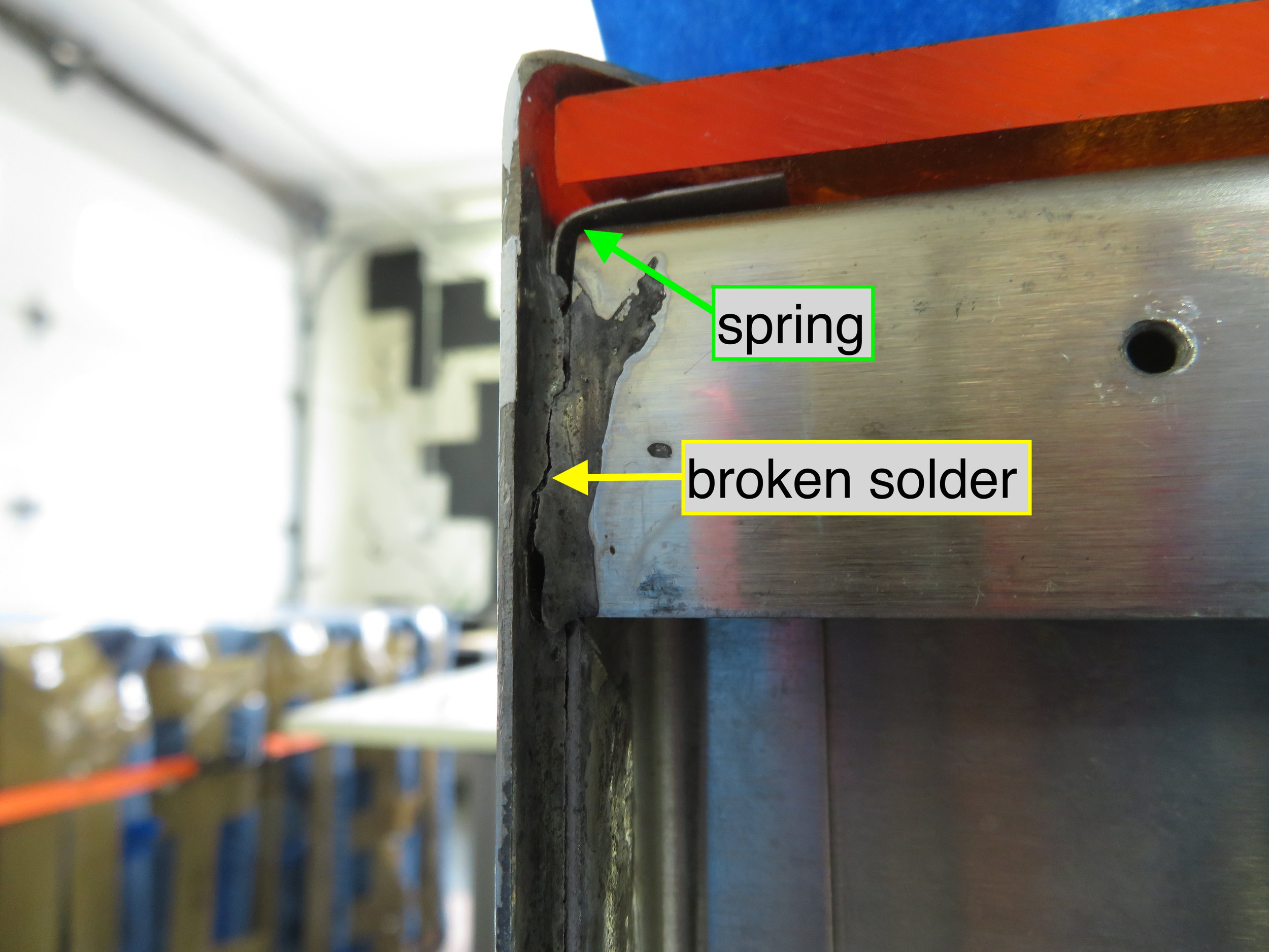 Spring holding acrylic in place and broken solder join