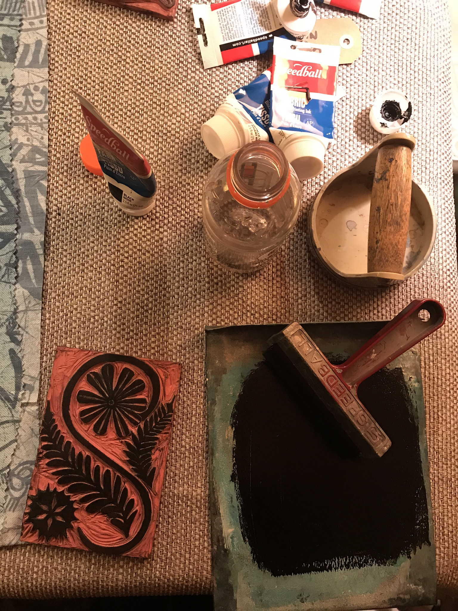 Ink That Up - So you can see all my tools and supplies here-I've got my baren for printing, my ink plate, speedball fabric ink tubes, my roller, and my cut unmounted lino block. I like to keep a bottle on water handy in case things dry up