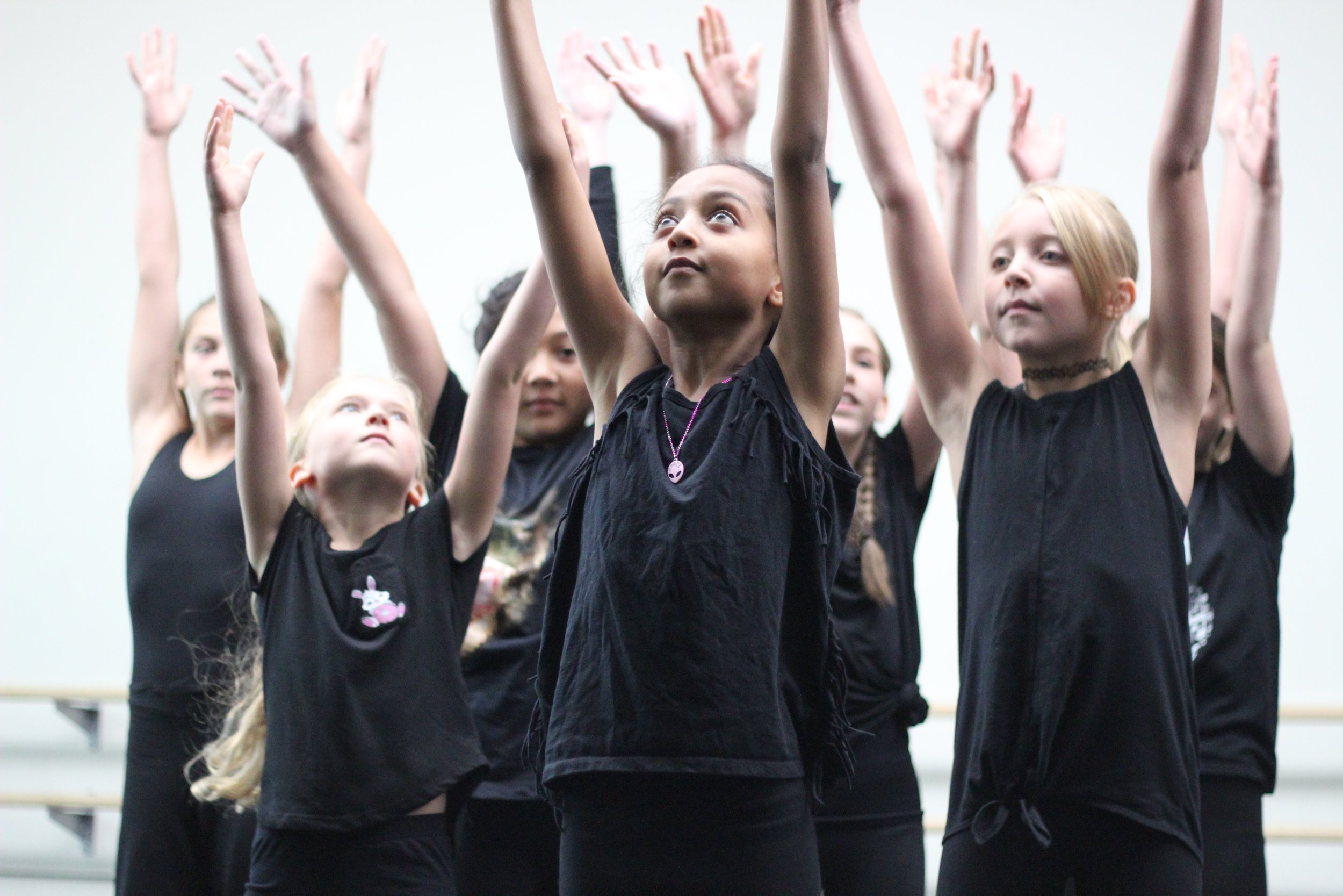 summer camp students with hands raised