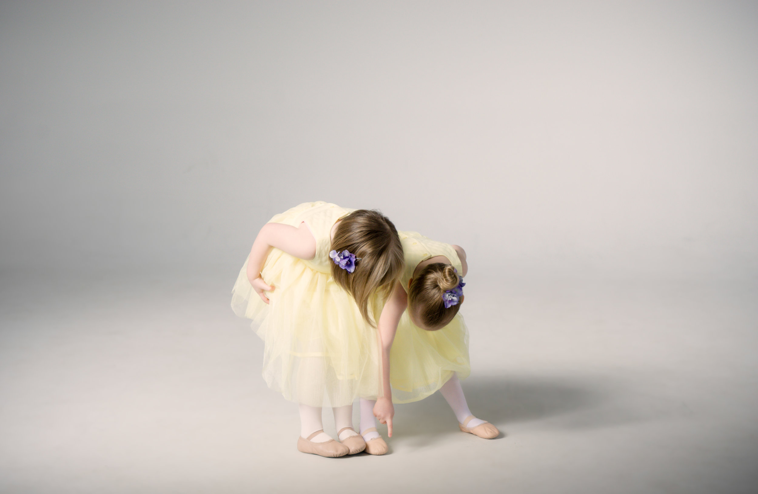 two children in yellow dresses pointing at toes