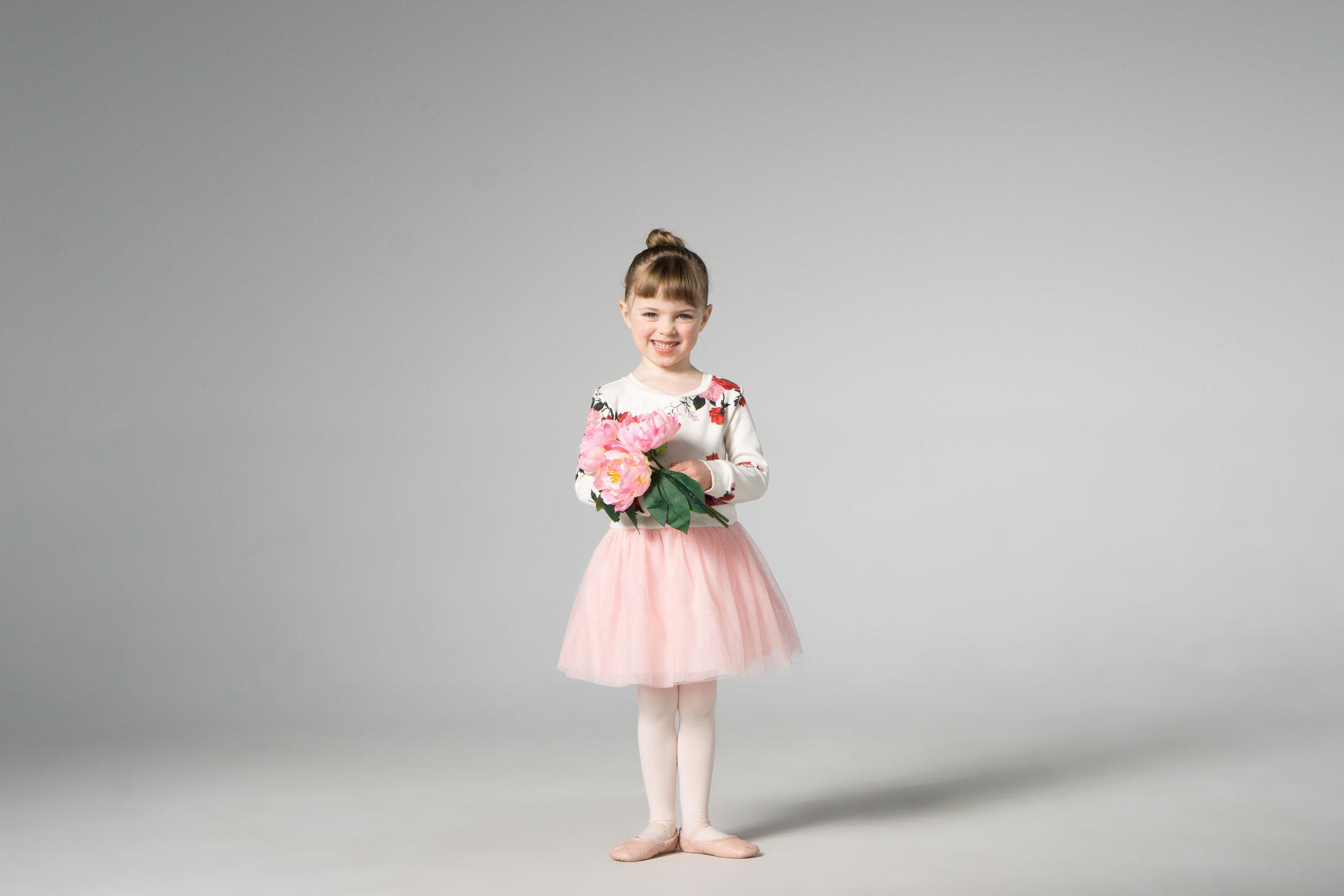 cute ballet dancer holding pink flowers