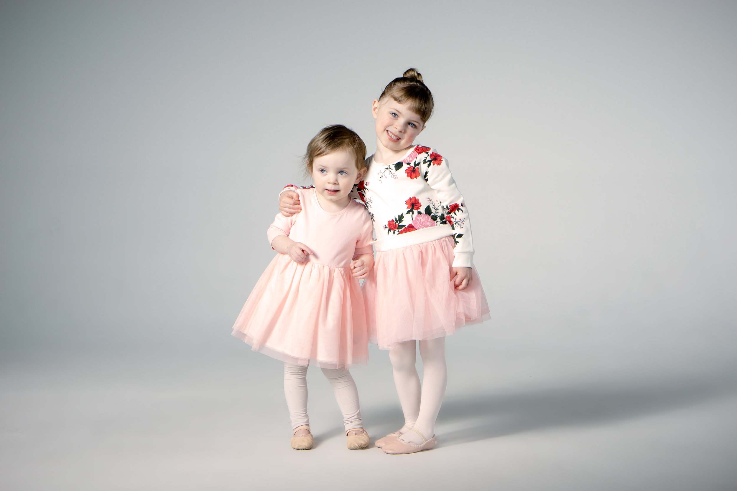 two young girls hugging in ballet outfits