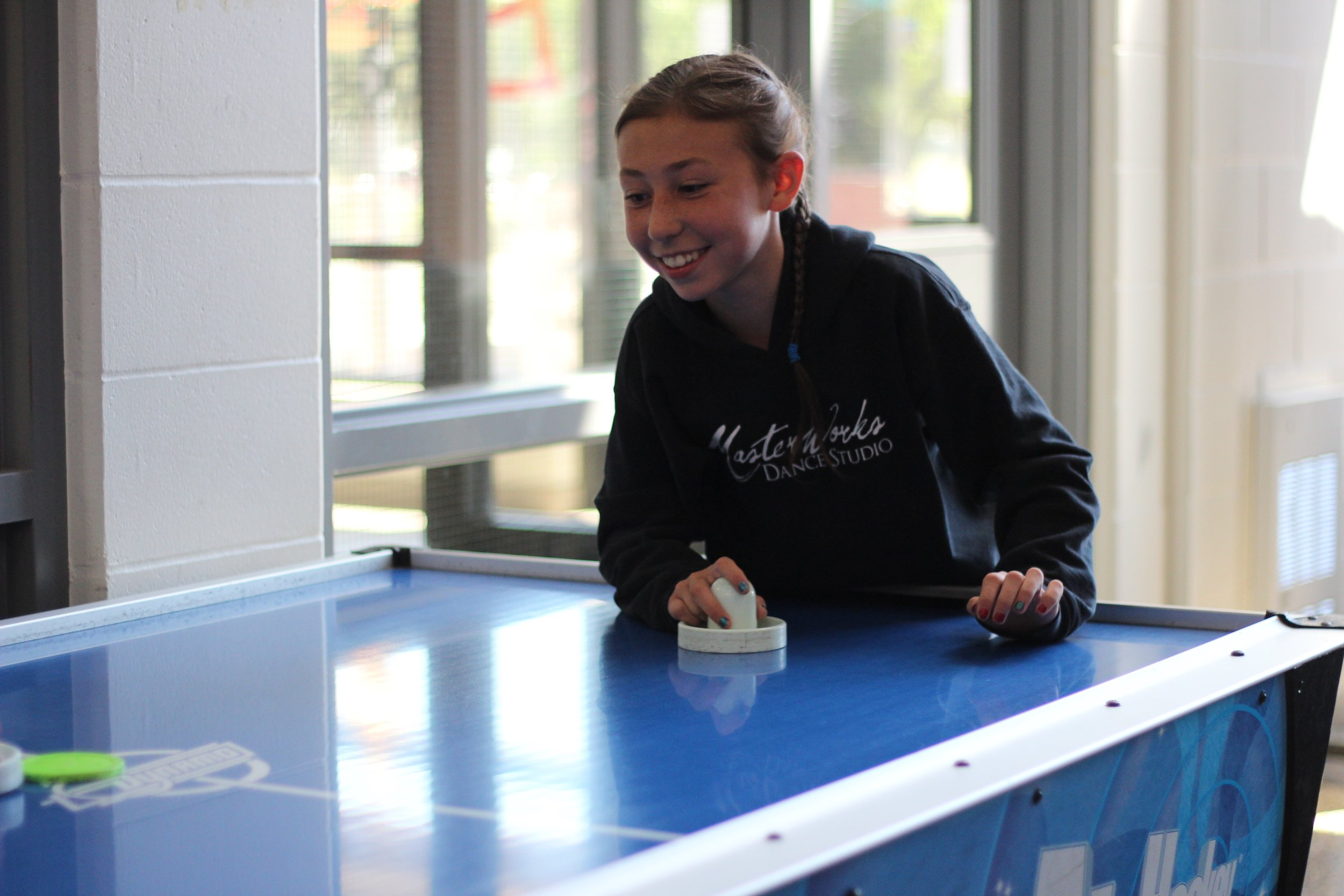 smiling girl playing air hockey