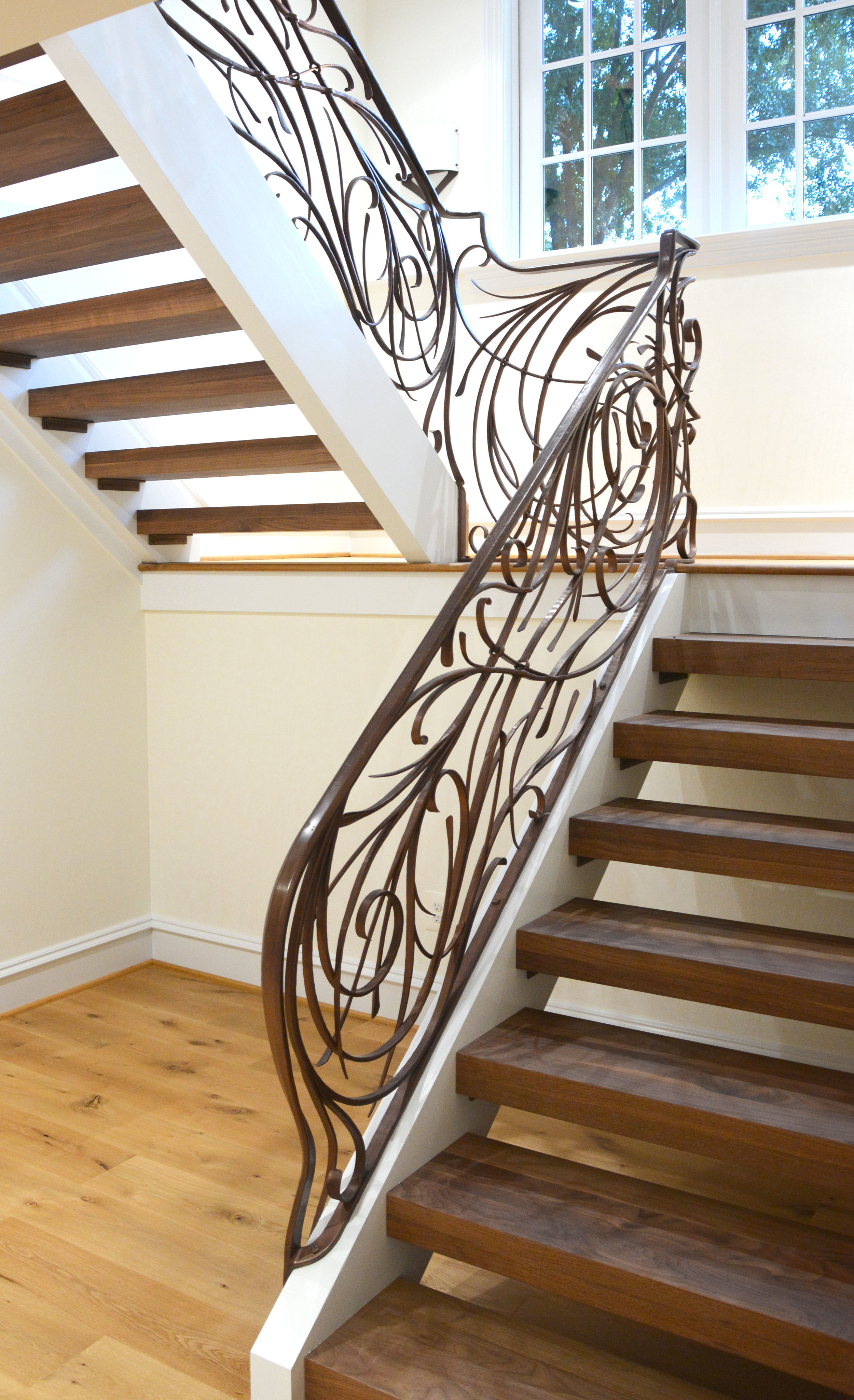The bottom of the railing ended with the cap rail swooping down and onto the side of the stair stringer, thus creating a beginning and end to the sculptural feeling of the whole piece.