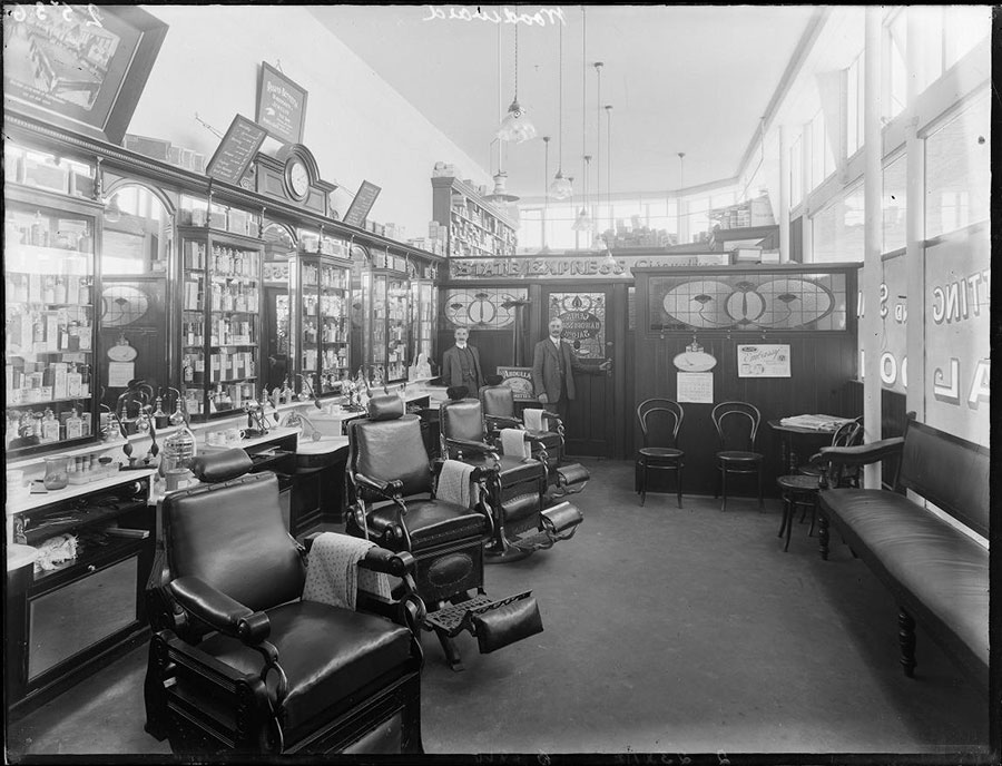 Woodward & Co. Barber Shop, circa 1914. Proprietor Frederick Woodward and his assistant stand poised at the door, as if to welcome an influx of gentlemen customers.