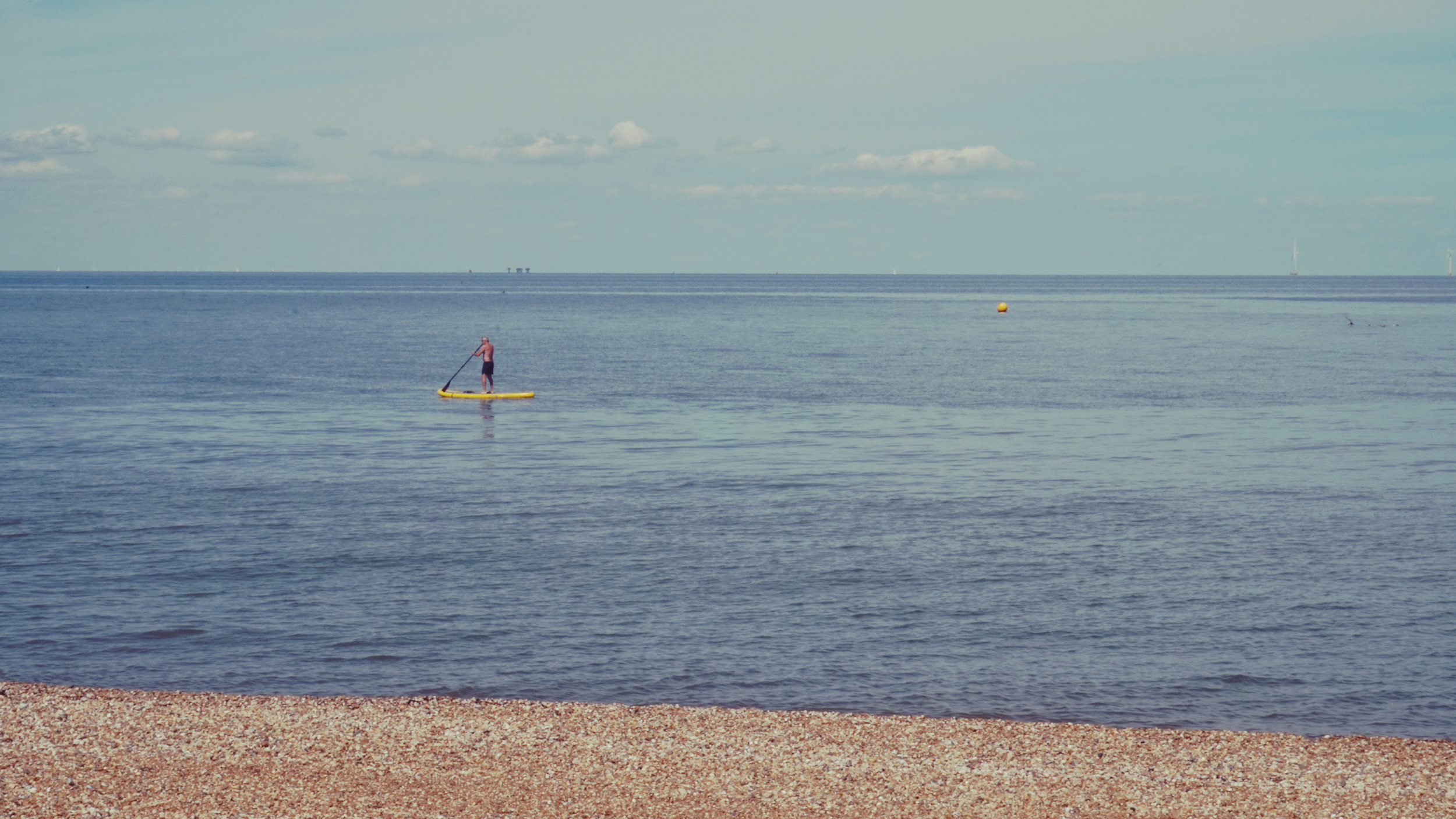 a man out at sea with a stand-up paddle board